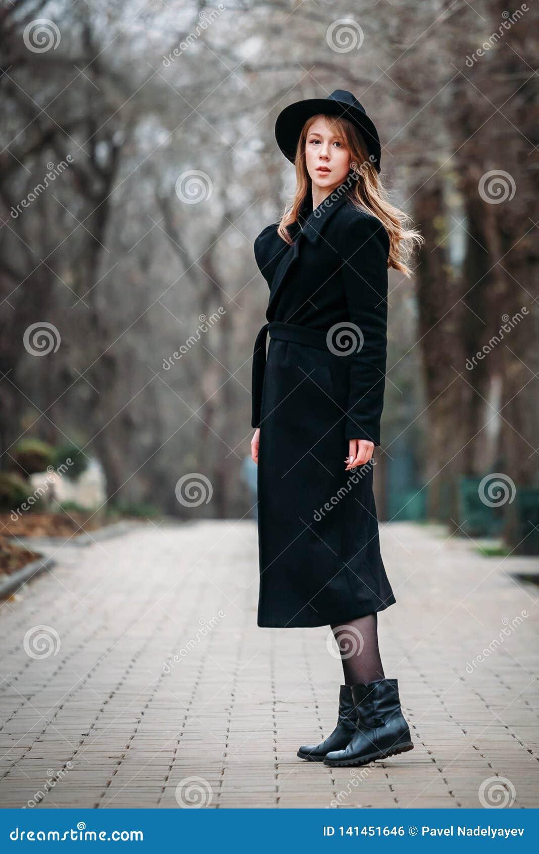 Utomhus- stående av en romantisk nätt elegant affär av en långhårig kvinna som tycker om en promenad till och med staden