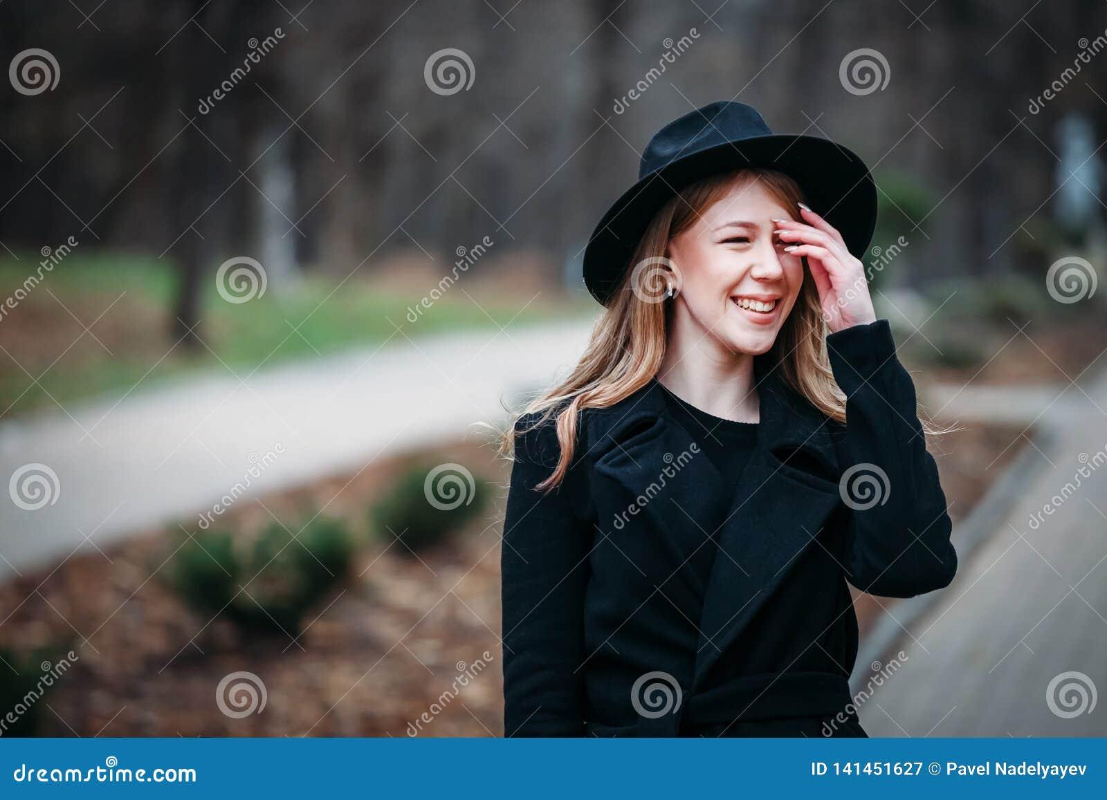 Utomhus- stående av en romantisk nätt elegant affär av en långhårig kvinna som tycker om en promenad till och med staden Foto av
