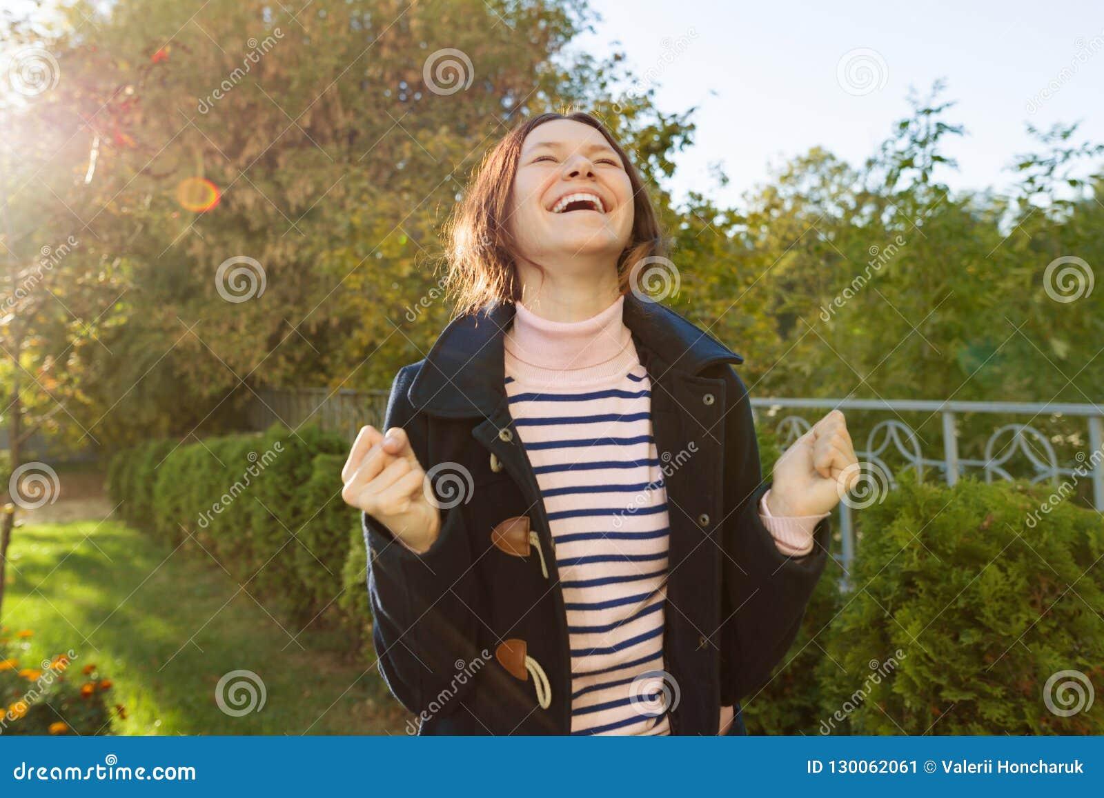 Utomhus- stående av en ung tonårig flicka med en sinnesrörelse av lycka, framgång, seger, guld- timme