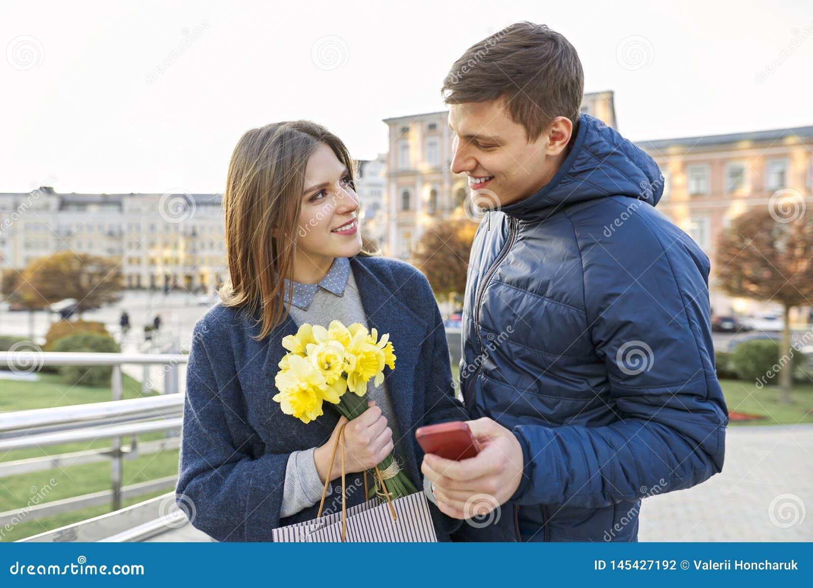 Utomhus- stående av härliga romantiska par, den unga mannen och kvinnan med buketten av gula blommor av påskliljor och att se in