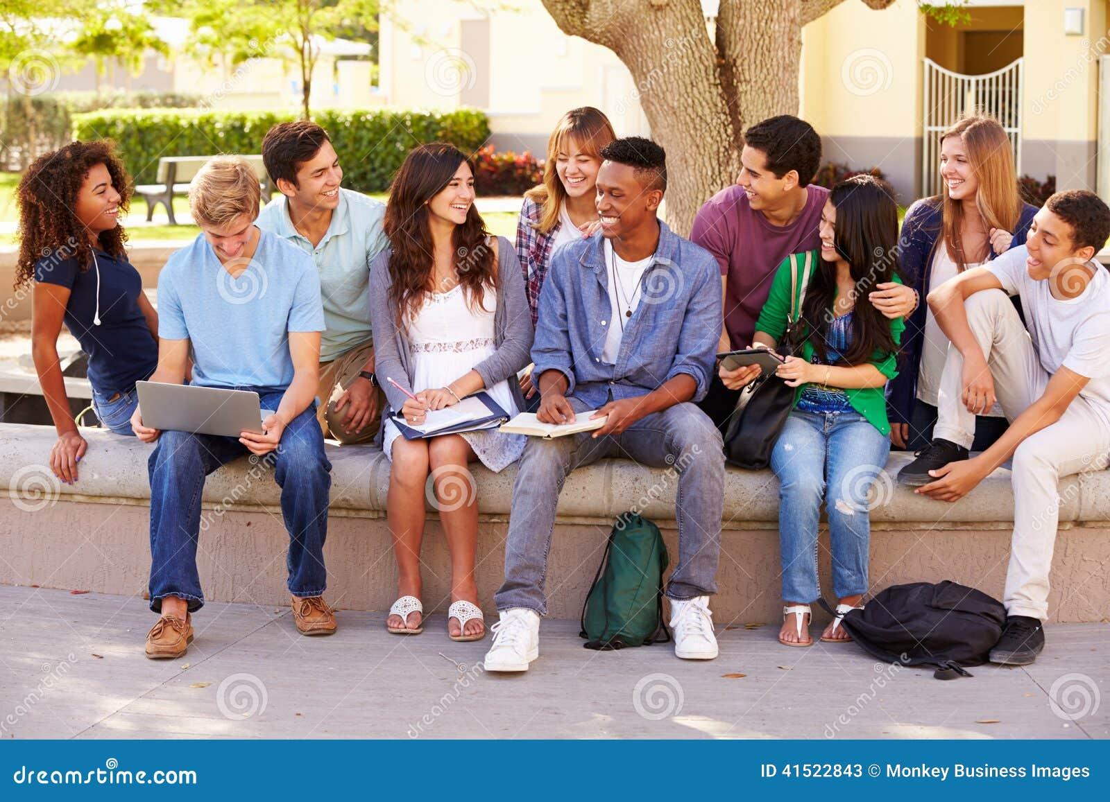 Utomhus- stående av högstadiumstudenter på universitetsområde