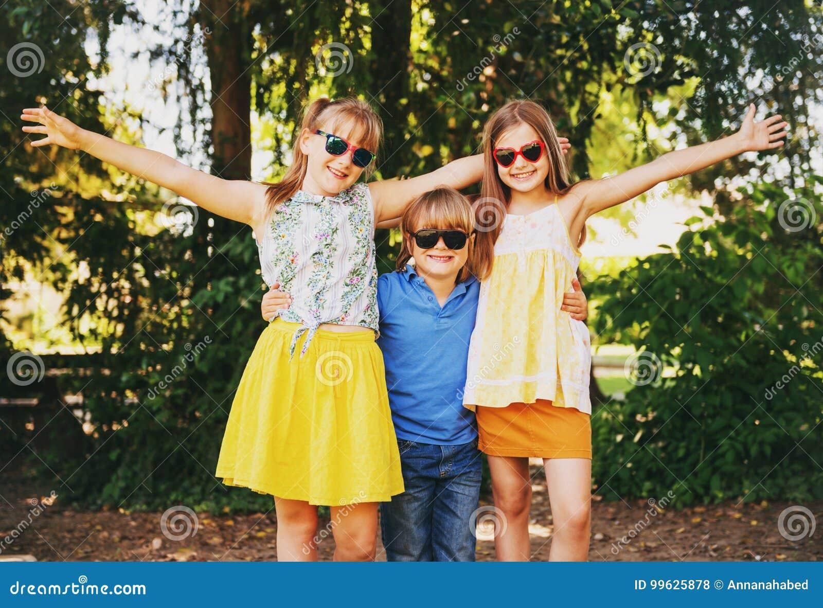 Utomhus- stående av 3 roliga ungar som tillsammans spelar