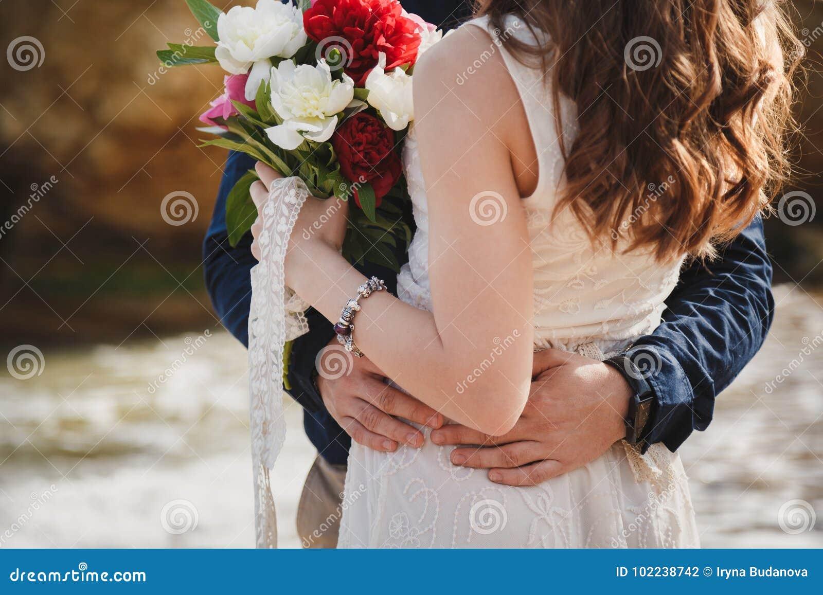 Utomhus- strandbröllopceremoni nära havet, slut upp av omfamningen av stilfulla par med bröllopbuketten, man kramar bruden