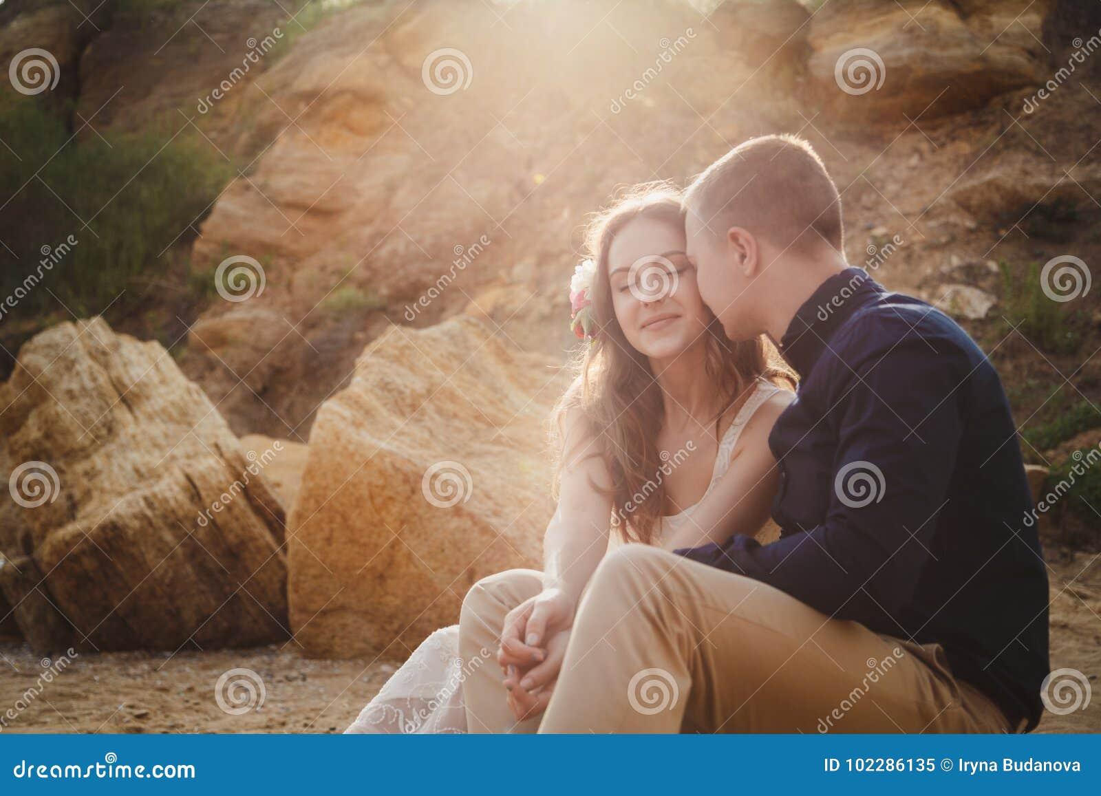 Utomhus- strandbröllopceremoni, slut upp av stilfulla lyckliga romantiska par som sitter tillsammans i solljus