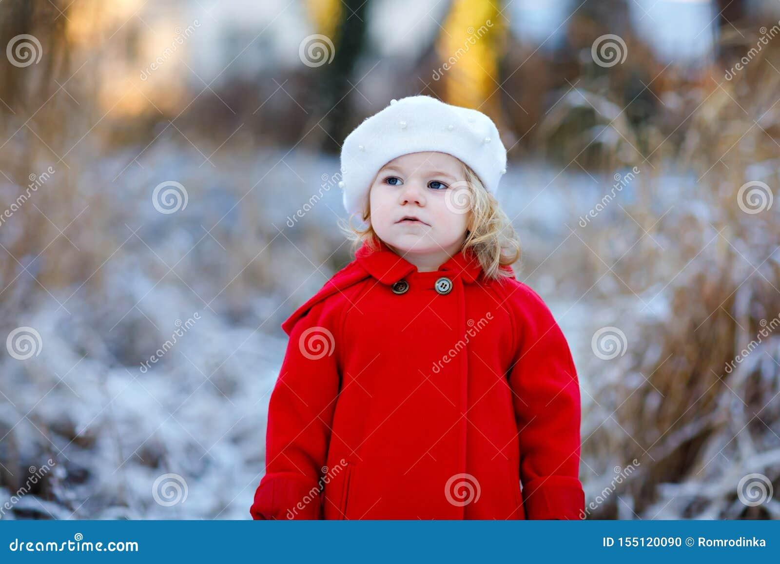 Utomhus- vinterst?ende av den lilla gulliga litet barnflickan i r?tt lag och den vita modehattbarreten Sunt lyckligt behandla som
