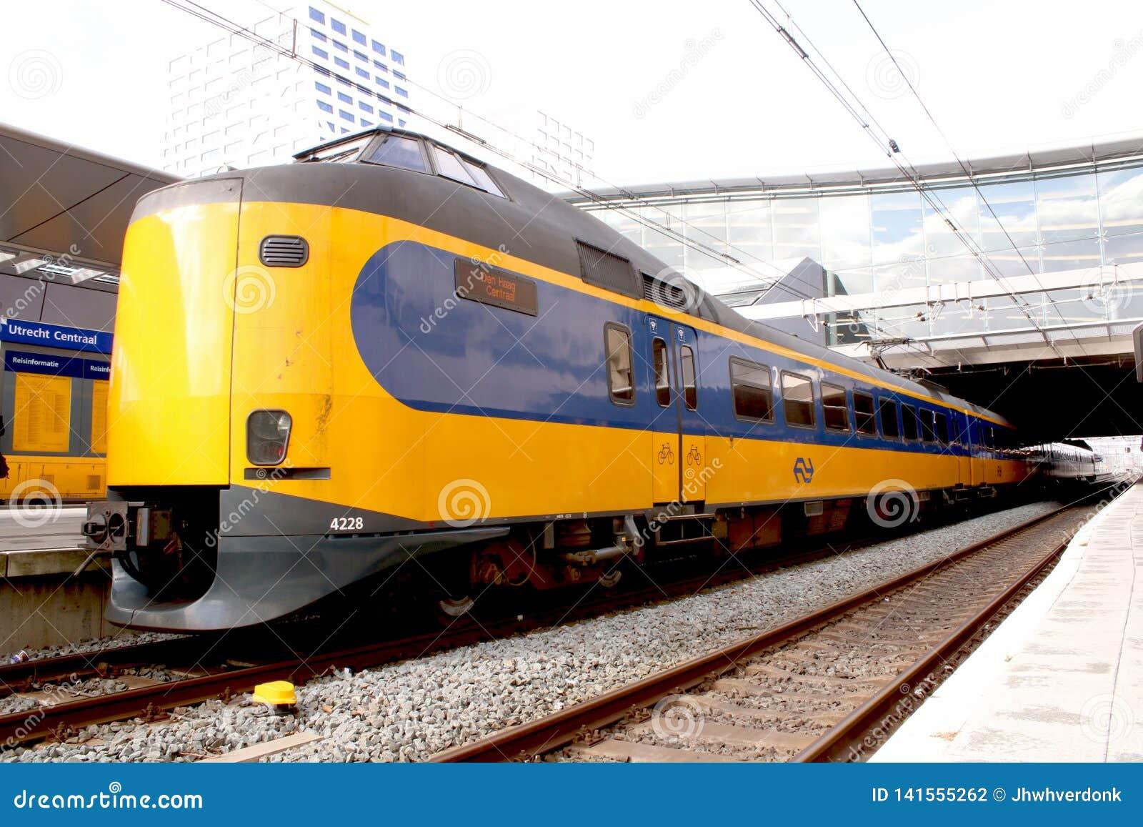Utrecht, Нидерланд, 8-ое марта 2019: желтый поезд, междугороднее готовое уйти от NS или spoorwegen nederlandse