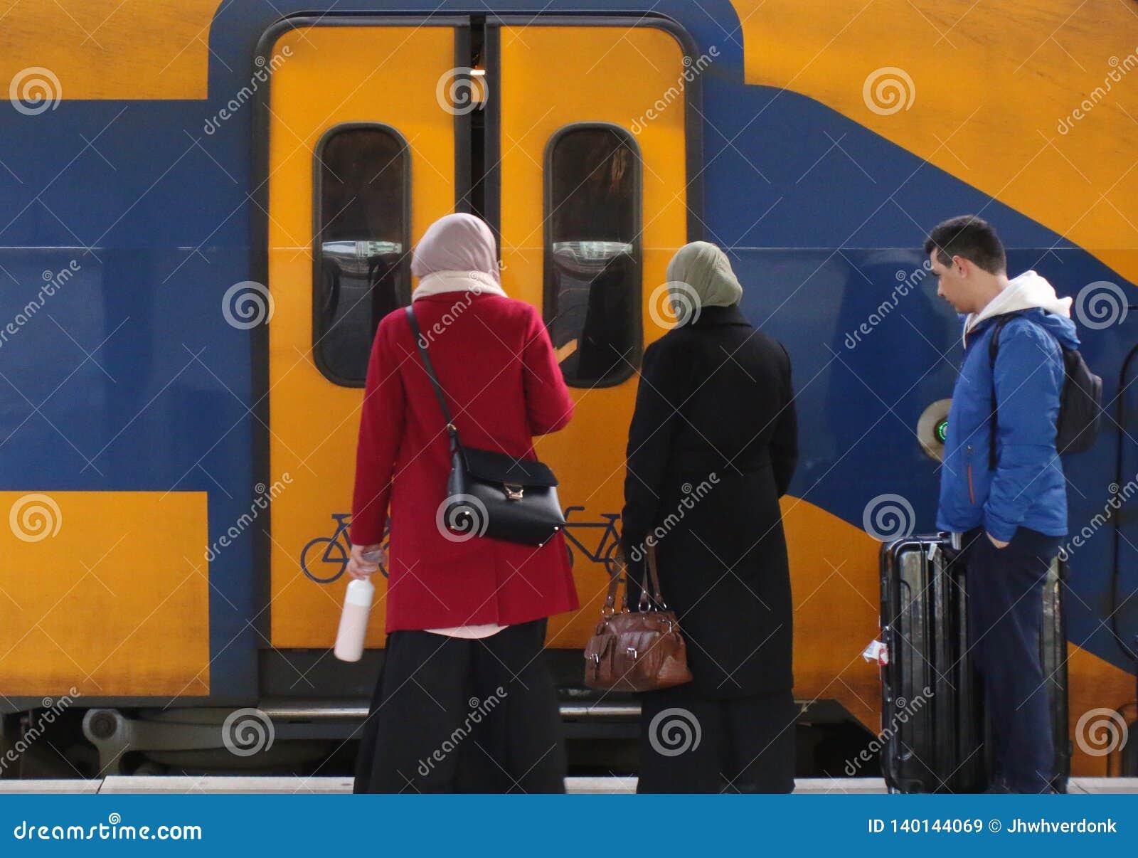 Utrecht, Нидерланд, 15-ое февраля 2019: 3 люд путешествуя с поездом и ждать двери для открытия