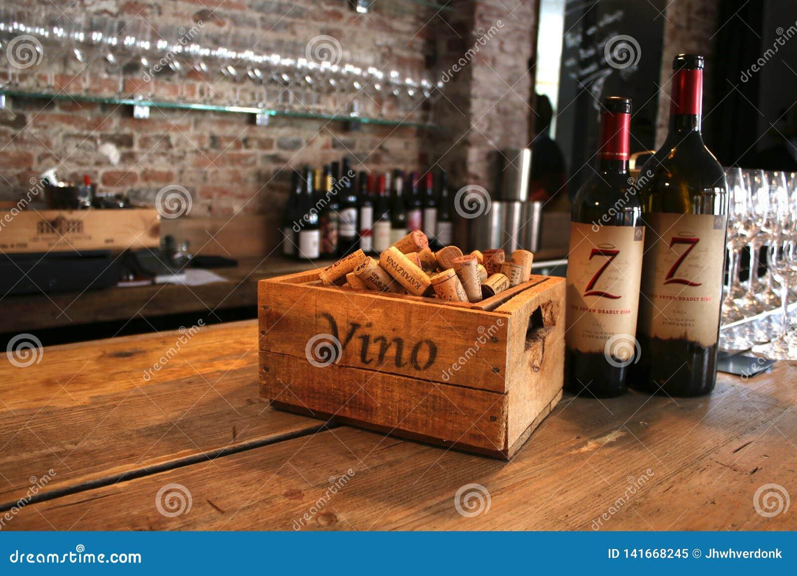Utrecht, el Netherland, el 10 de marzo - 2019: Bar de vinos puesto con los corchos de madera y dos botellas de vino