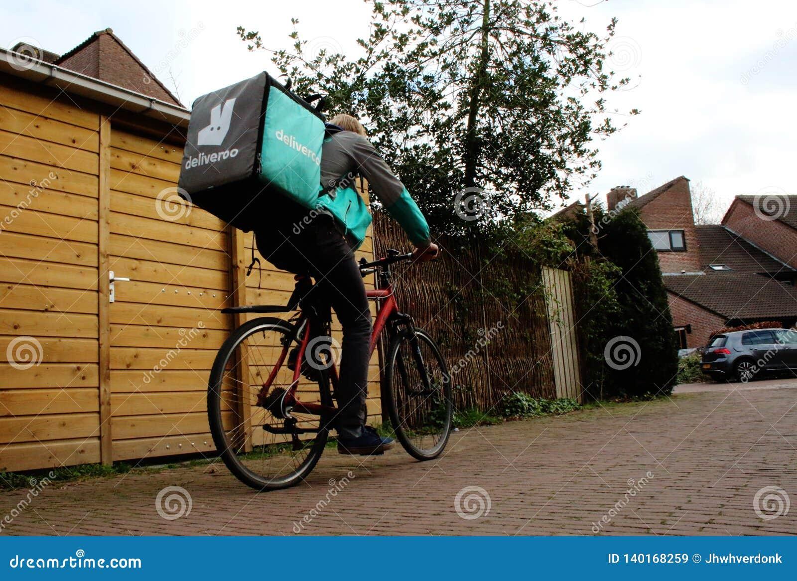 Utrecht holandie, Luty 19, 2019: Deliveroo freelancer na jego rowerze iść następna dostawa