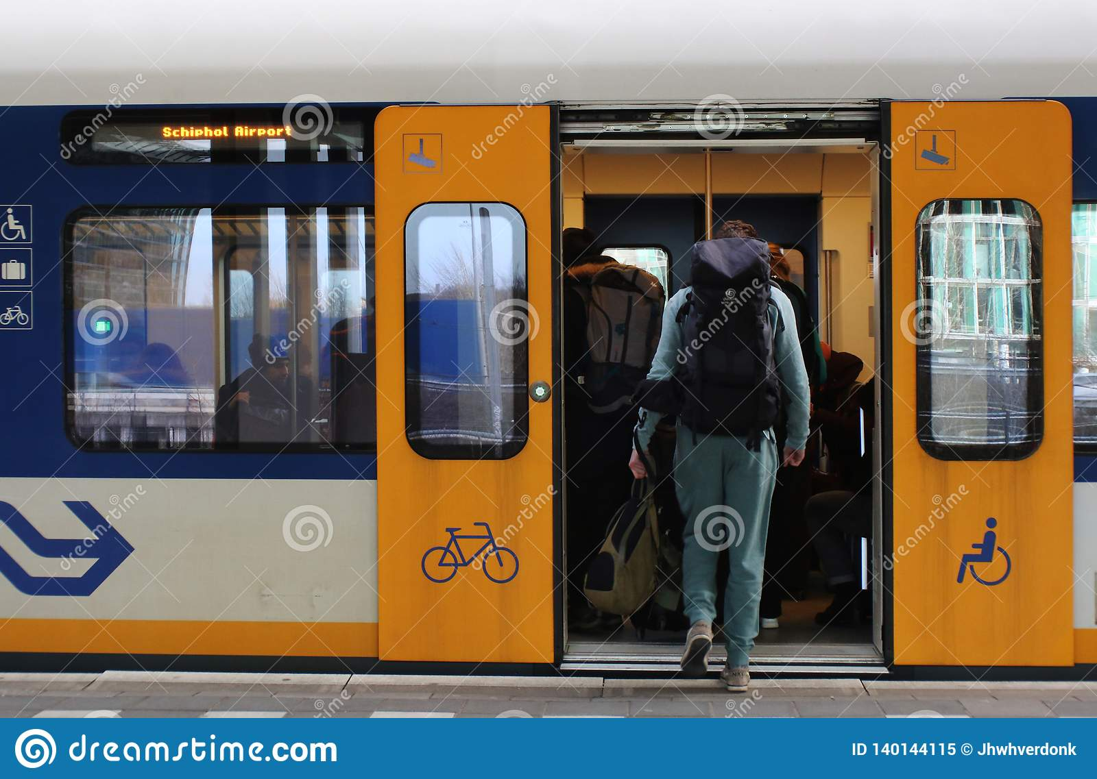 Utrecht, the Netherlands, February 15, 2019: A traveller with backback catching a train sprinter in the netherlands