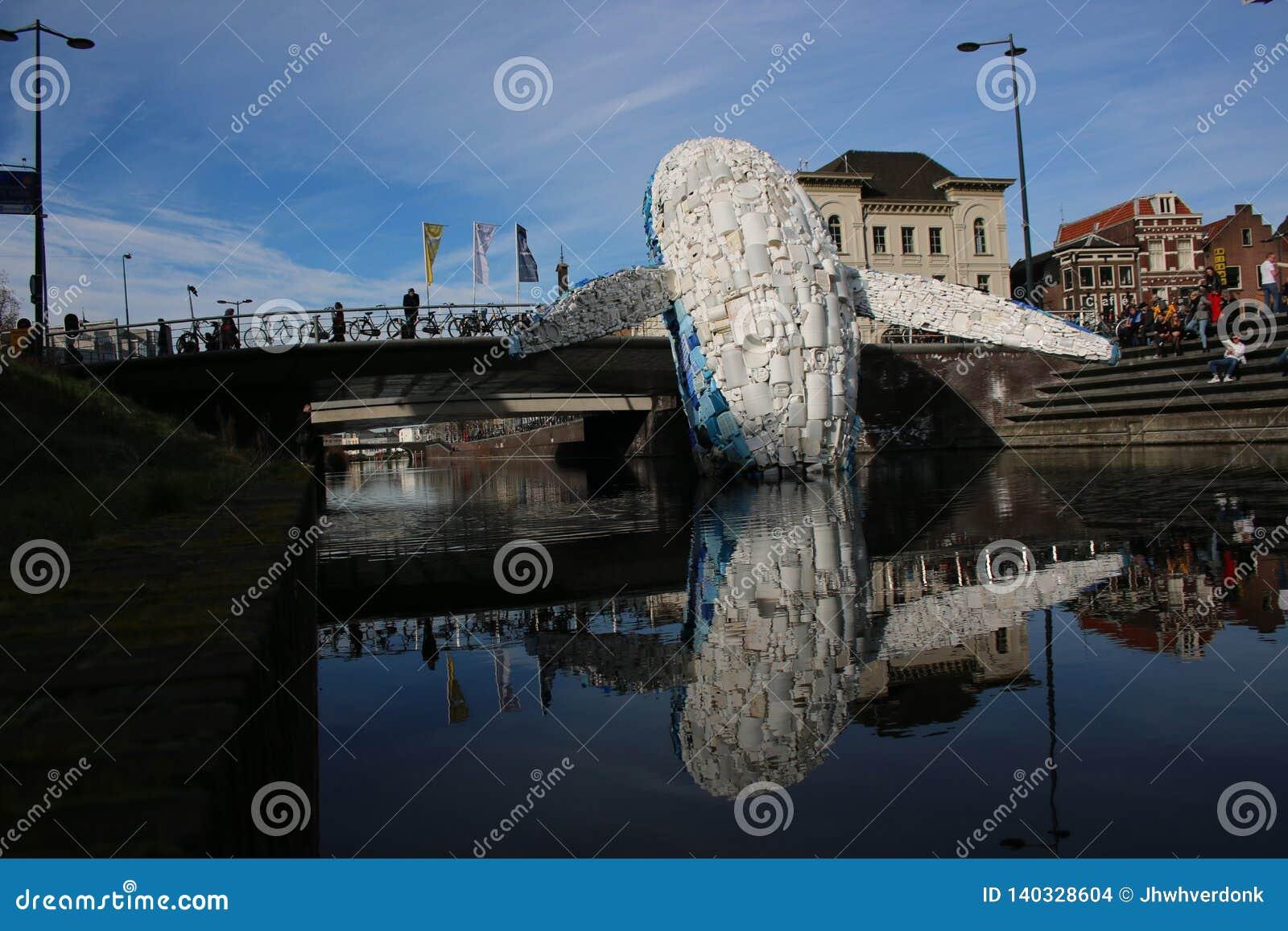 Utrecht, os Países Baixos, o 24 de fevereiro - 2019, baleia feita do desperdício plástico no canal contra a poluição