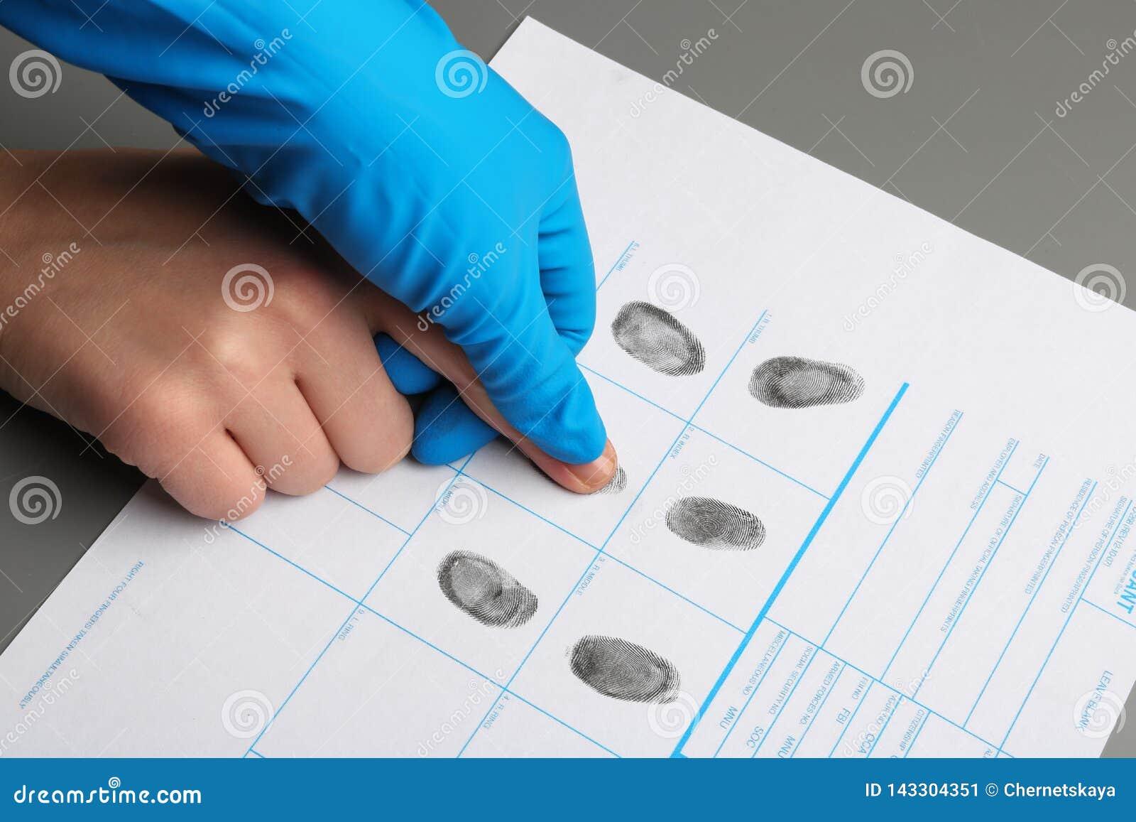 Utredare som tar fingeravtryck av misstänkten på tabellen Brottslig sakkunskap