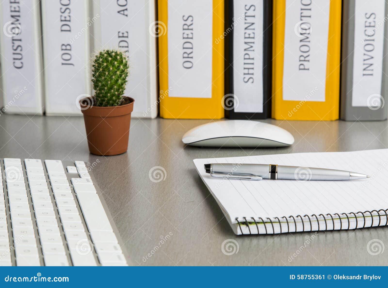 Utrymme för kontorsarbete på det gråa skrivbordet med kaktuns och