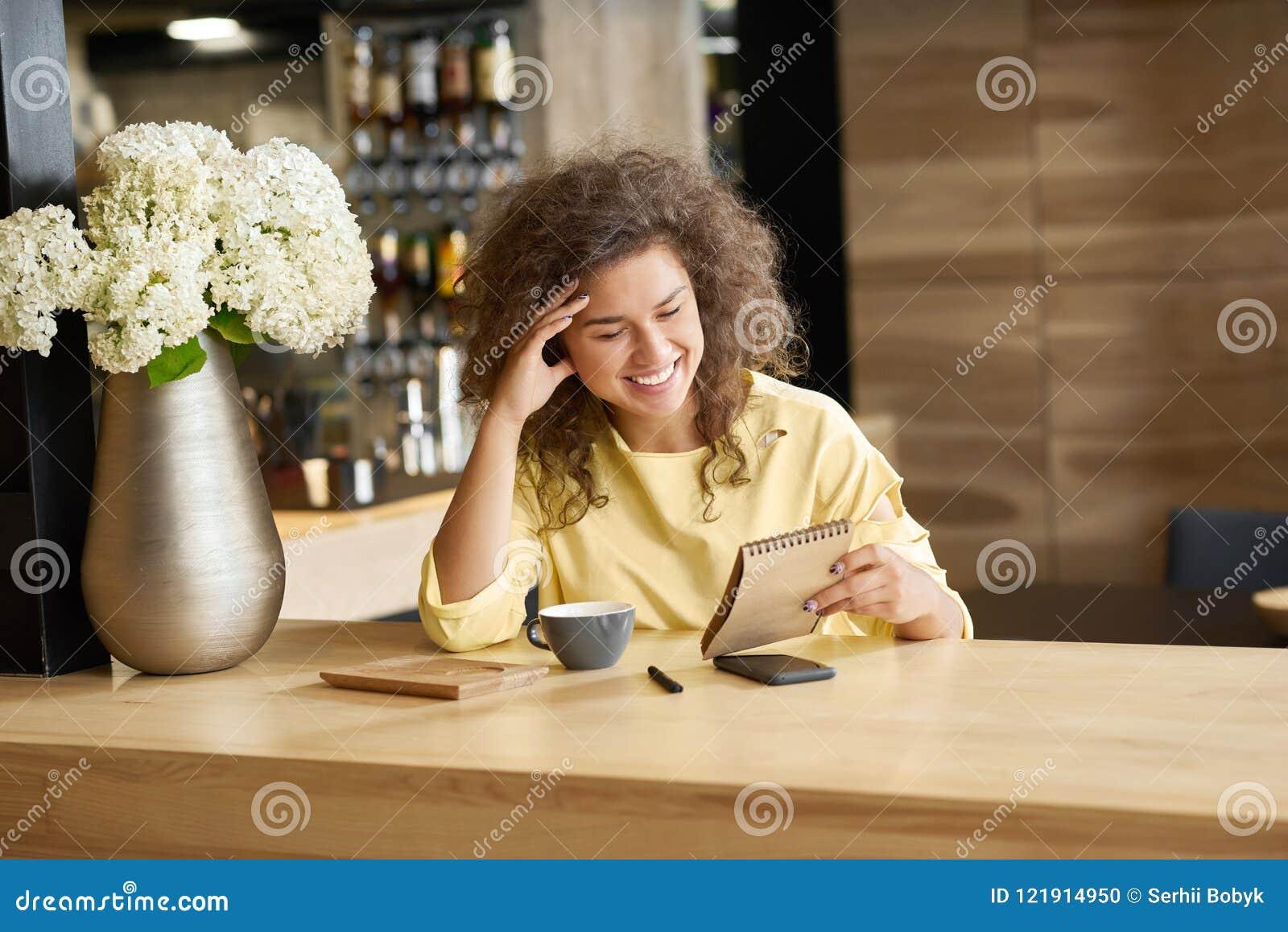 Utsmyckat skratta ung flickasammanträde på trätabellen som håller blocknote