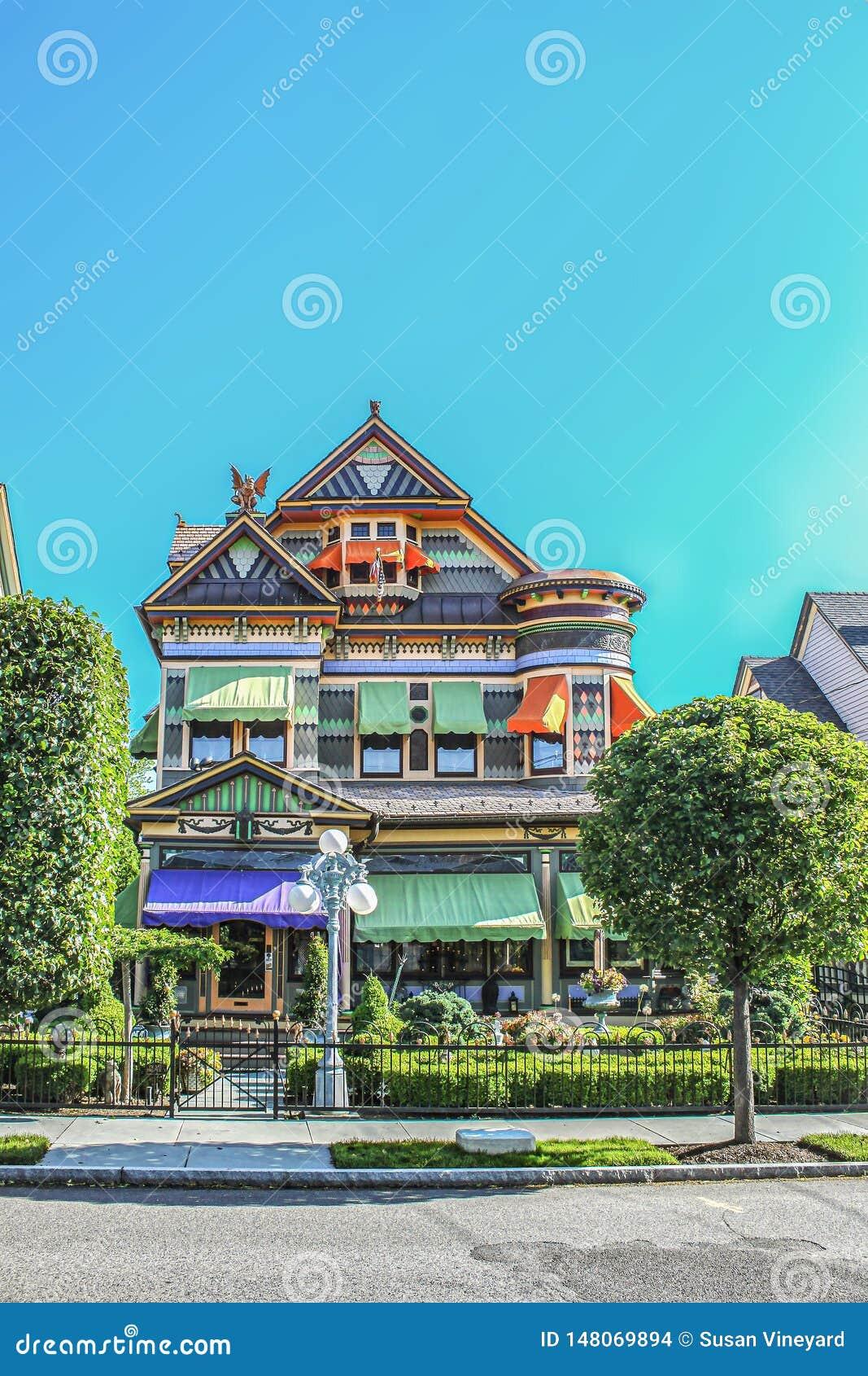 Utsmyckat viktorianskt hus som överst klippas med pepparkakan och ljusa färger med tornet och vattenkastaren av vindskupefönstret