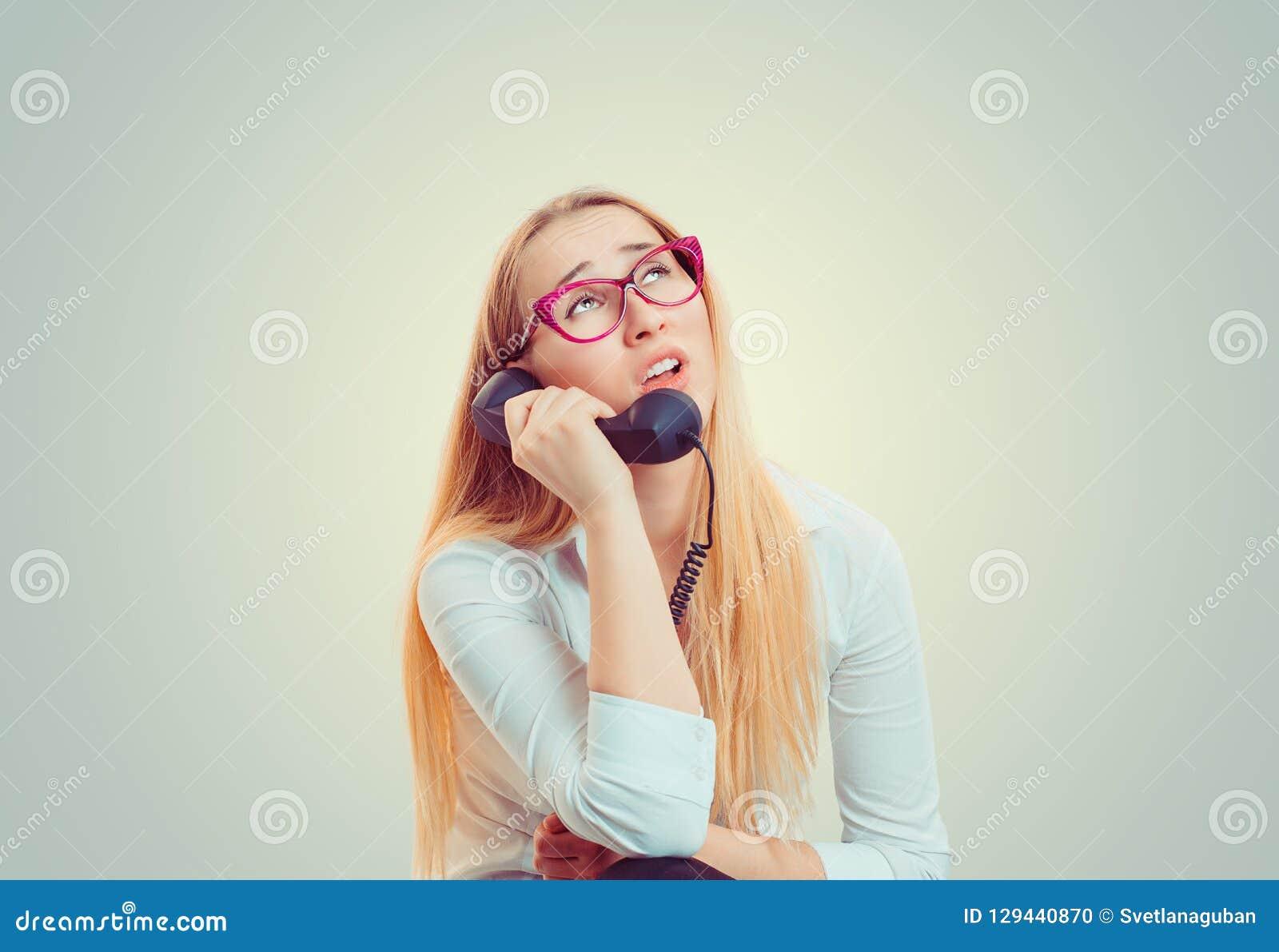 Uttråkad kvinna som talar på telefonen