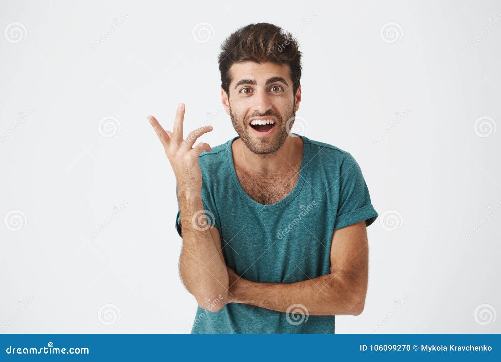 Uttryck, sinnesrörelser och känslor för mänsklig framsida Förvånad och förvånad skäggig ung man i blå t-skjorta som pekar på
