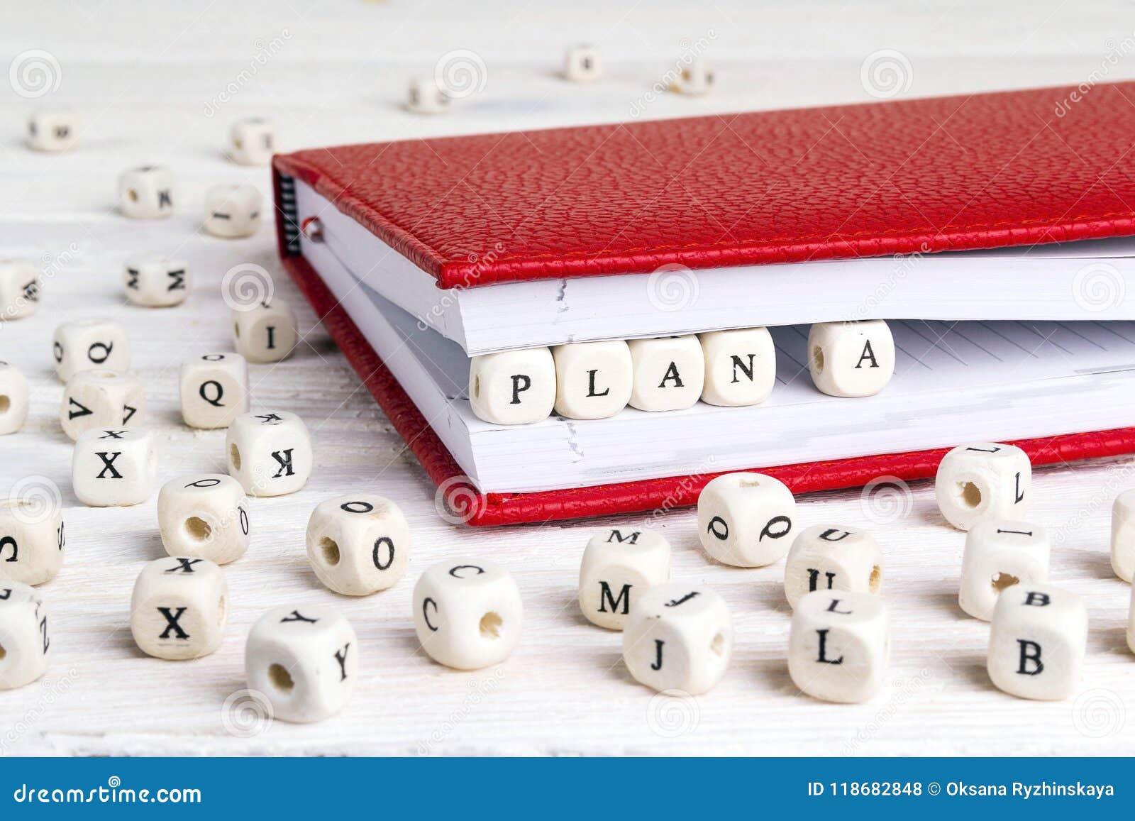 Uttrycka plan A som är skriftligt i träkvarter i röd anteckningsbok på den vita trätabellen