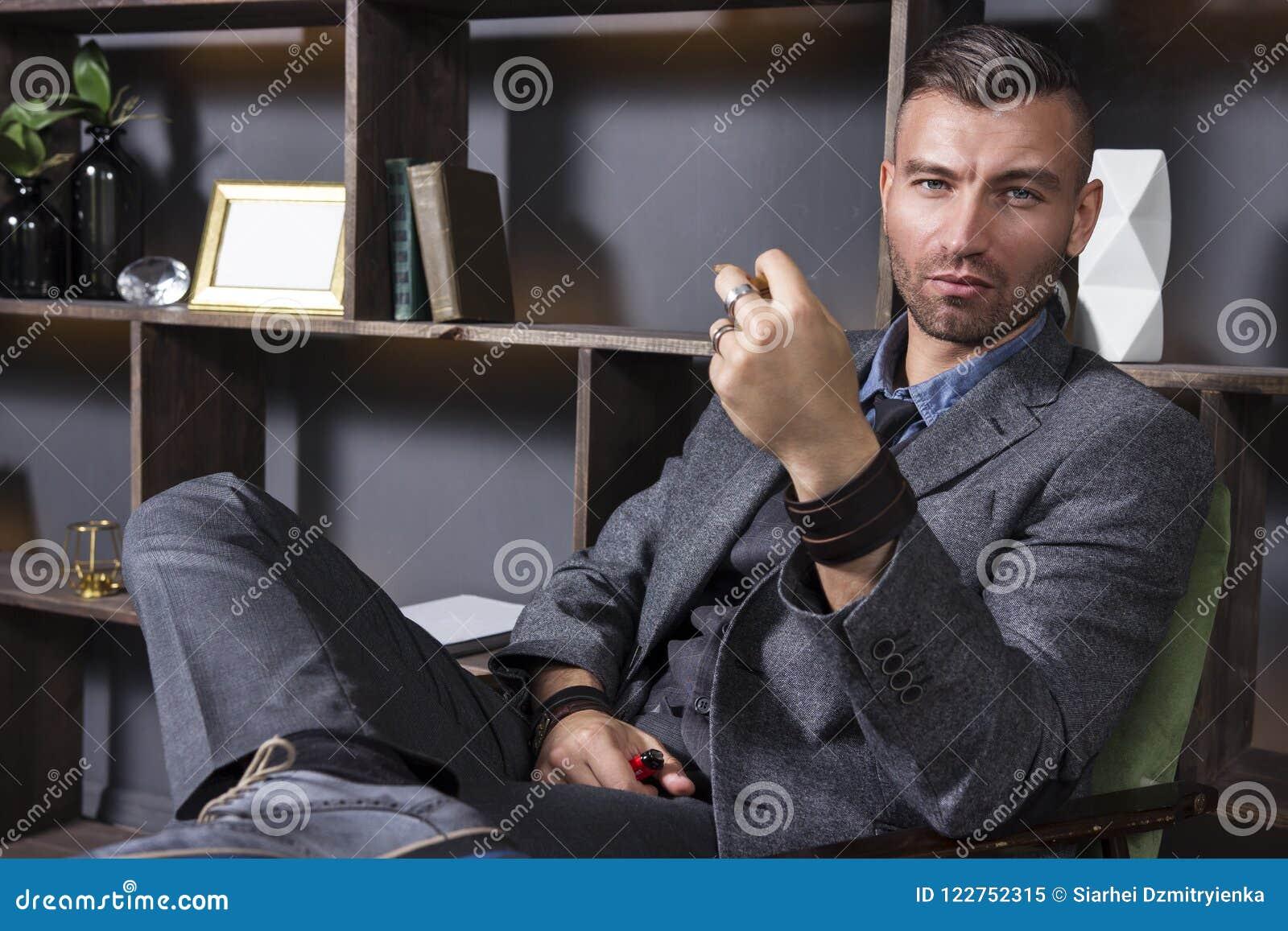 Uttrycksfull blick av en stilig man i en affärsdräkt, som sitter i en stol i en lyxig lägenhet med ett röka rör