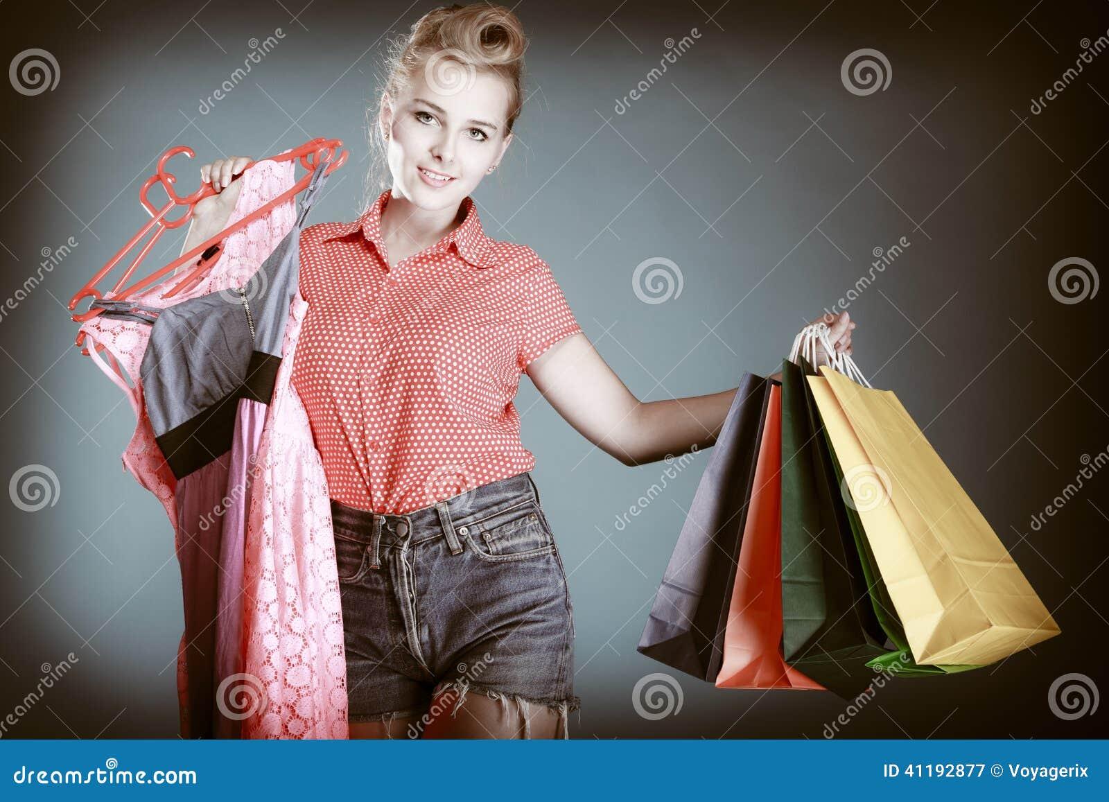 Utvikningsbrudflicka med shoppingpåsar som köper kläder försäljning