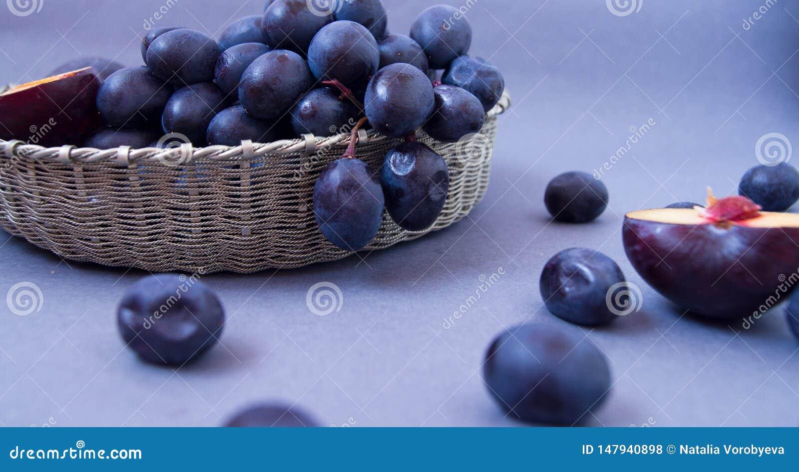 Uva e prugne in una ciotola d argento su un fondo scuro
