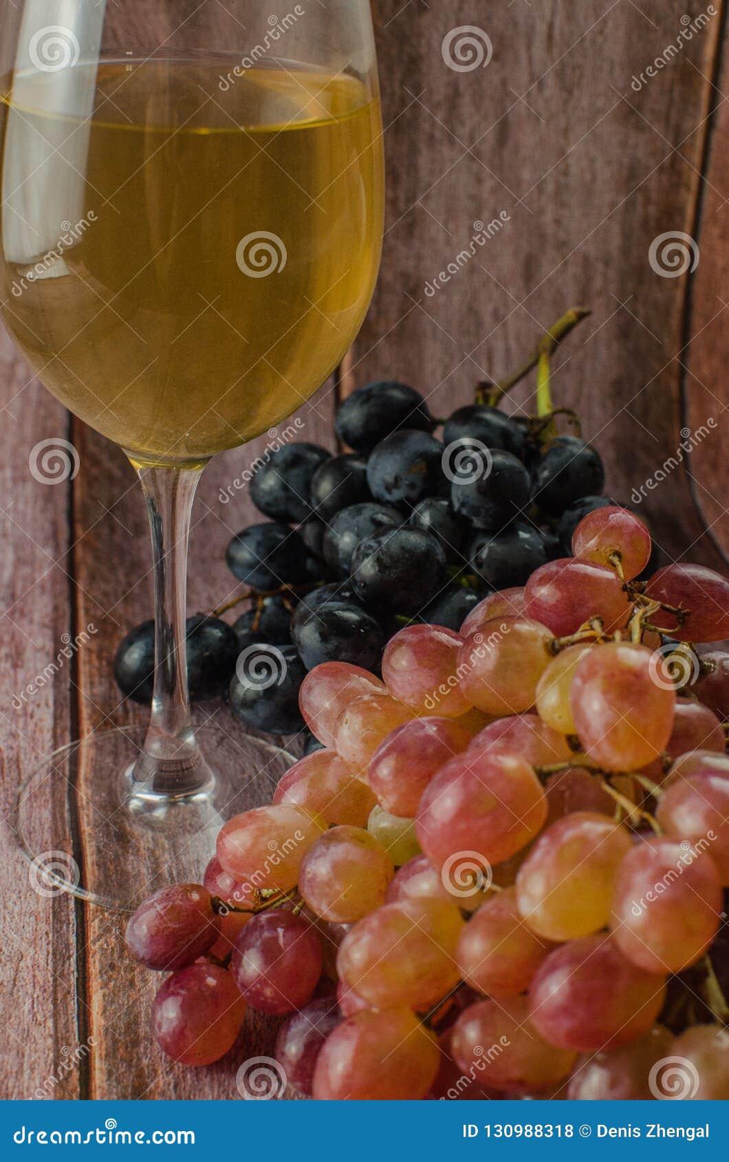 Uvas azules con la consumición sana de la hoja verde, aislado