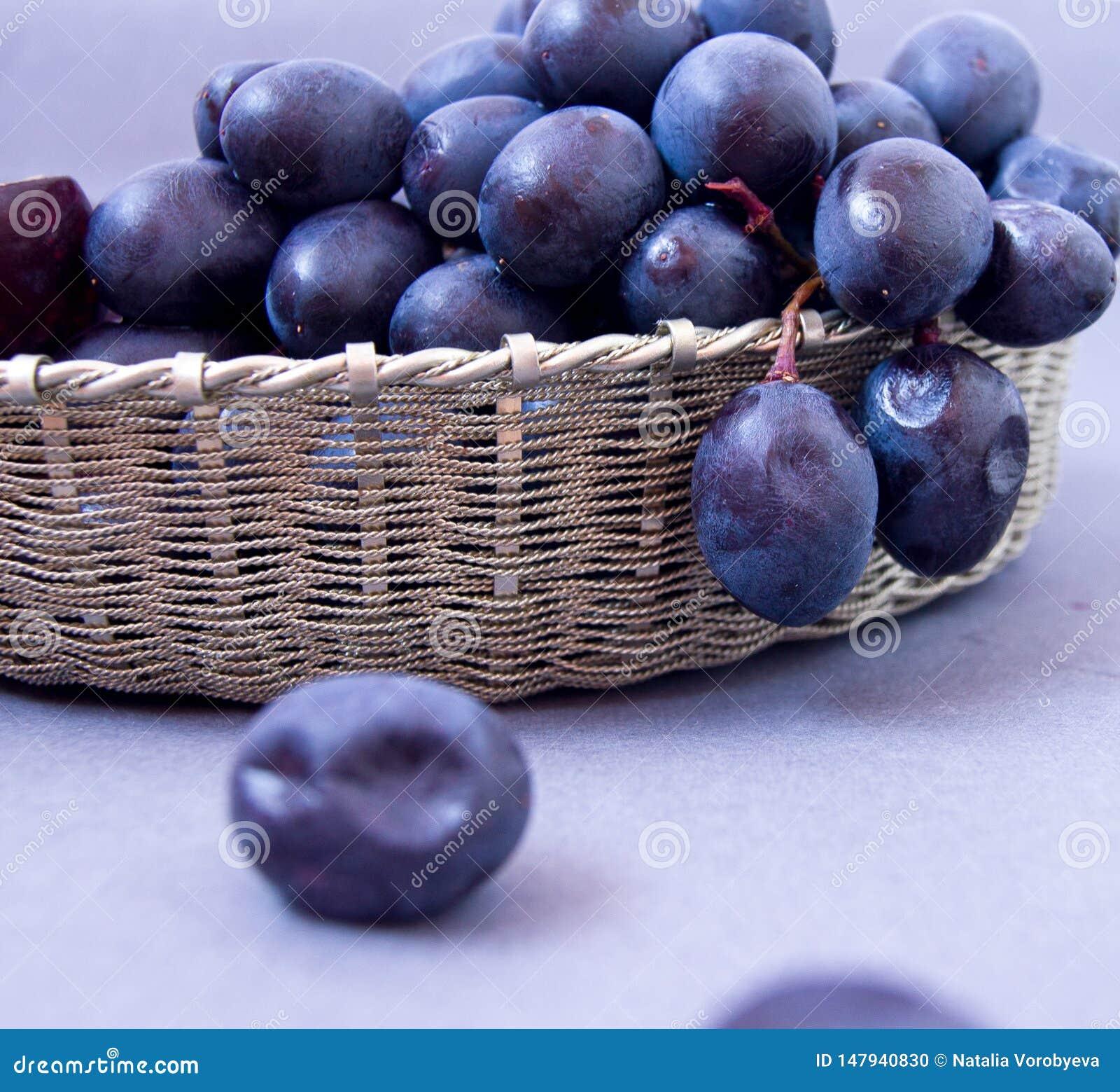 Uvas pretas em uma cesta de prata em um fundo cinzento