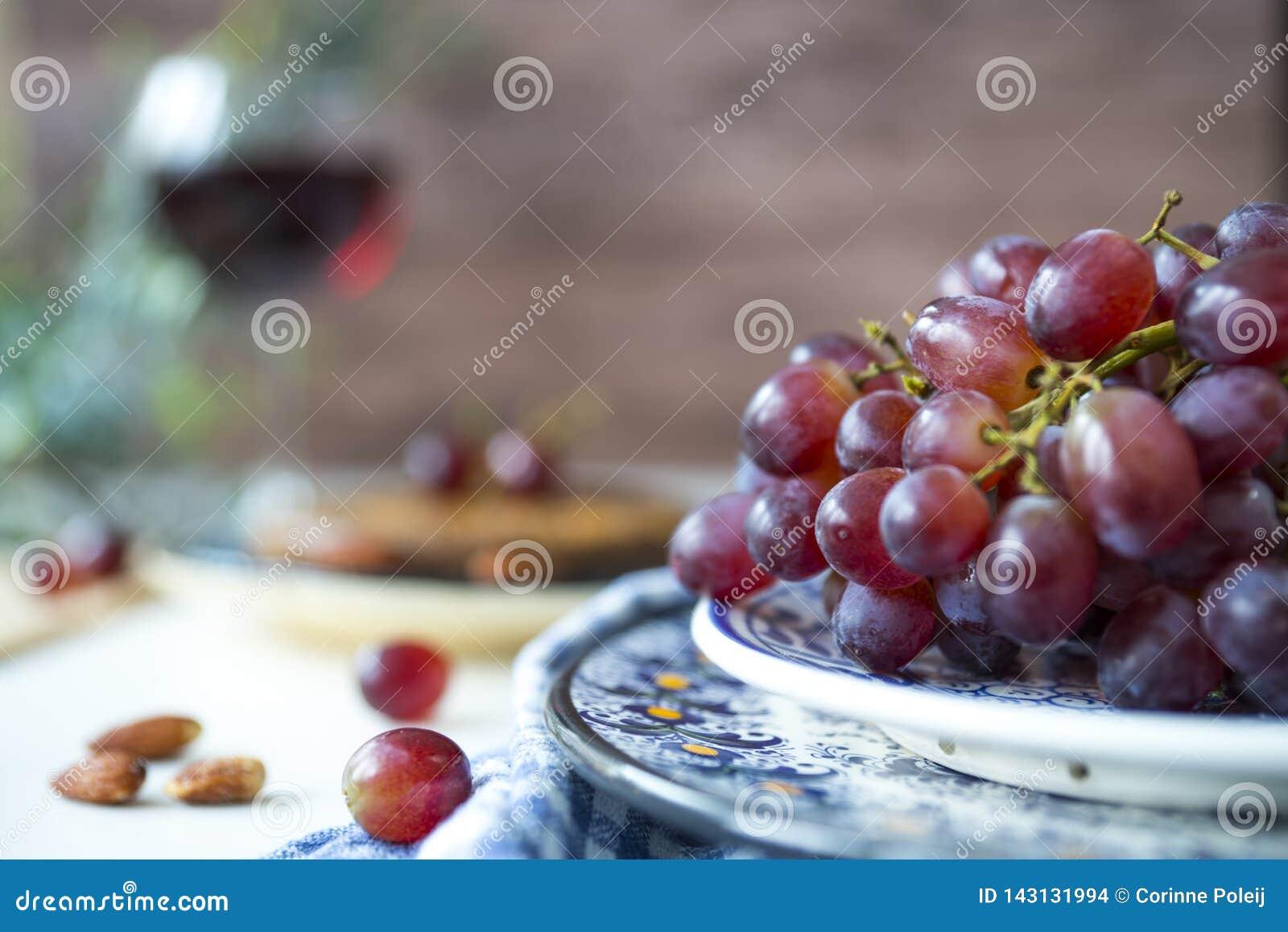 Uvas rojas del manojo en cuenco azul, contra fondo marrón de la falta de definición