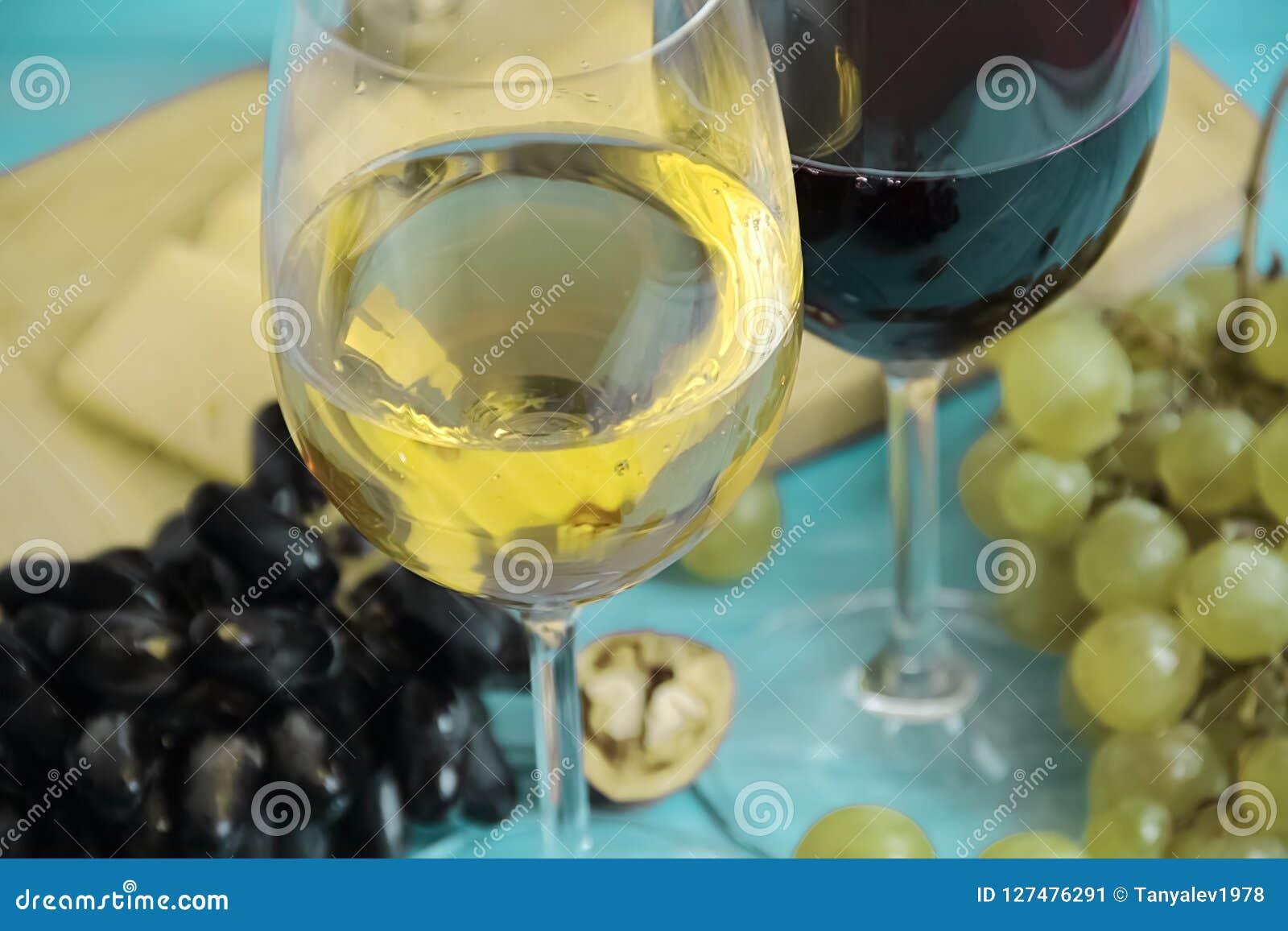 Uvas, um vidro do queijo rústico da bebida do outono da porca do vinho em um backgrounnut de madeira azul
