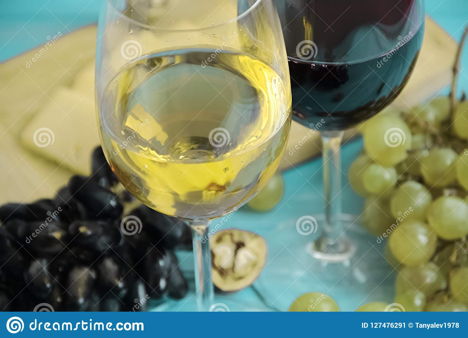 Uvas, un vidrio de queso rústico de la bebida del otoño de la nuez del vino en un backgrounnut de madera azul