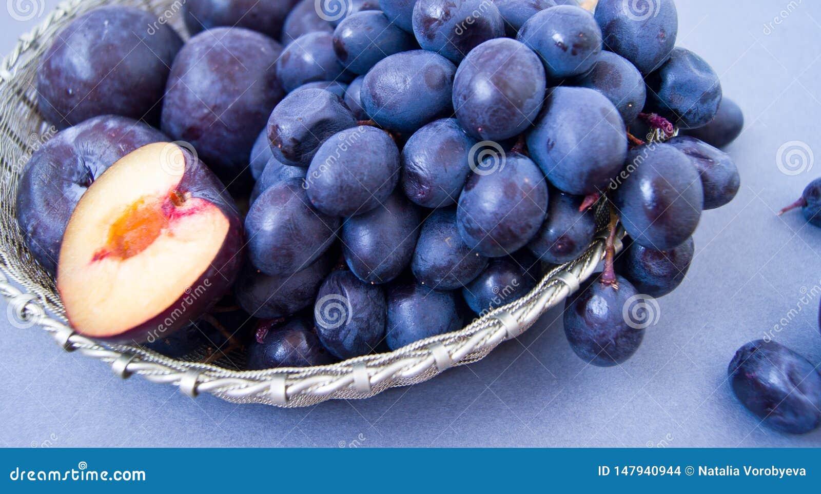 Uvas y ciruelos en un cuenco de plata