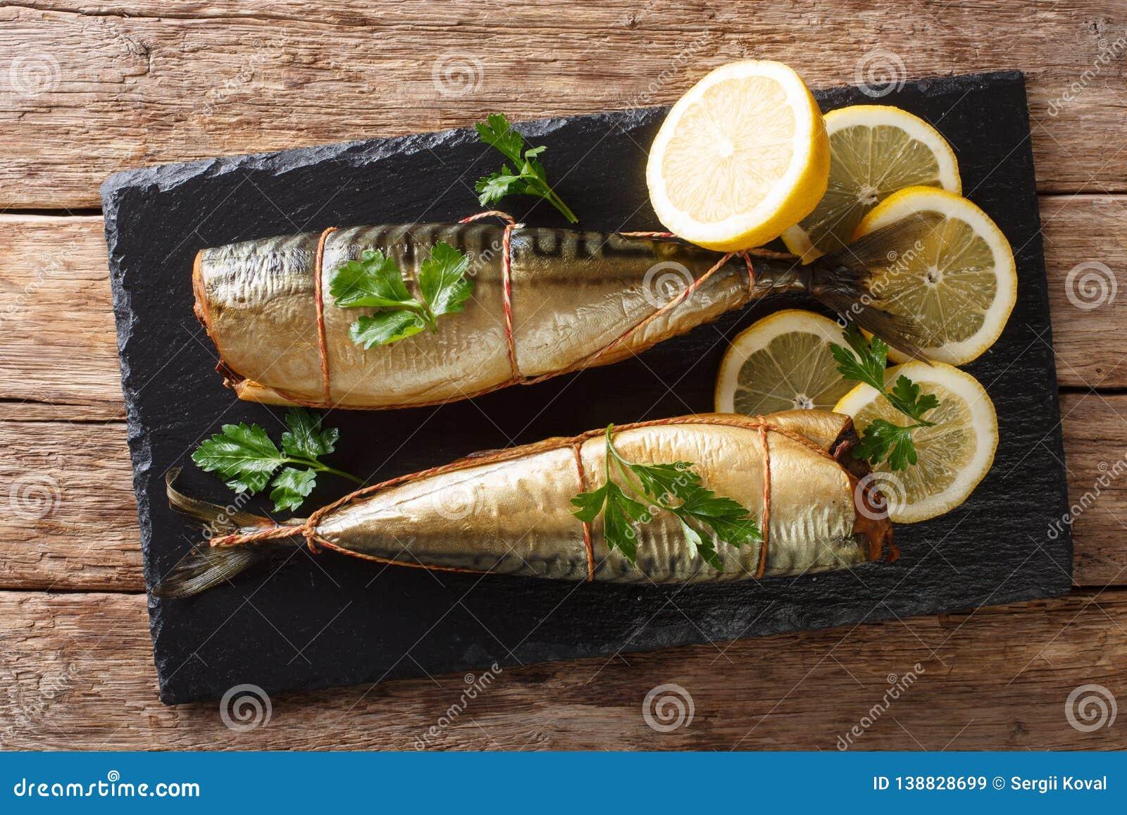 Uwędzona makrela z cytrynami i pietruszki zbliżenie na krytykujemy deskę na stole horyzontalny odgórny widok