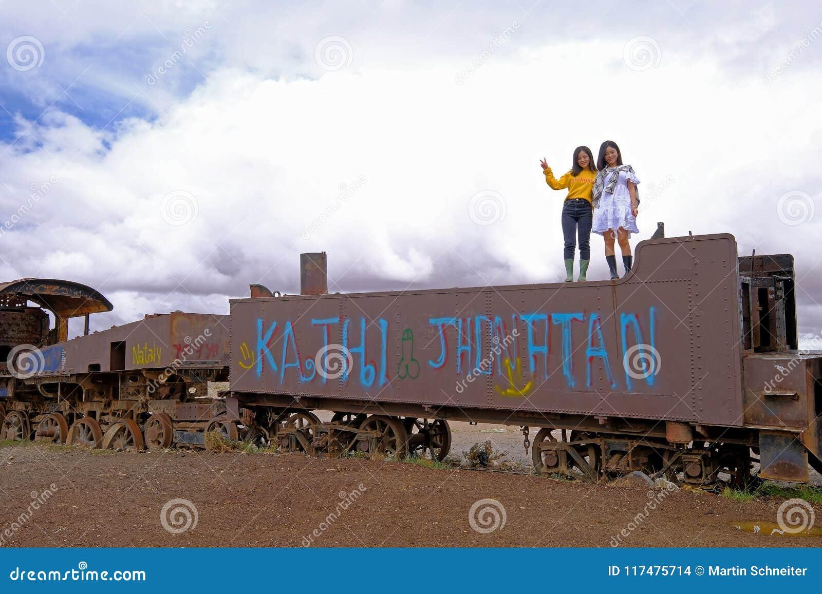 Uyuni, Bolivia, el 31 de enero de 2018: Dos turistas chinos que se colocan en un tren oxidado en el cementerio del tren, turismo