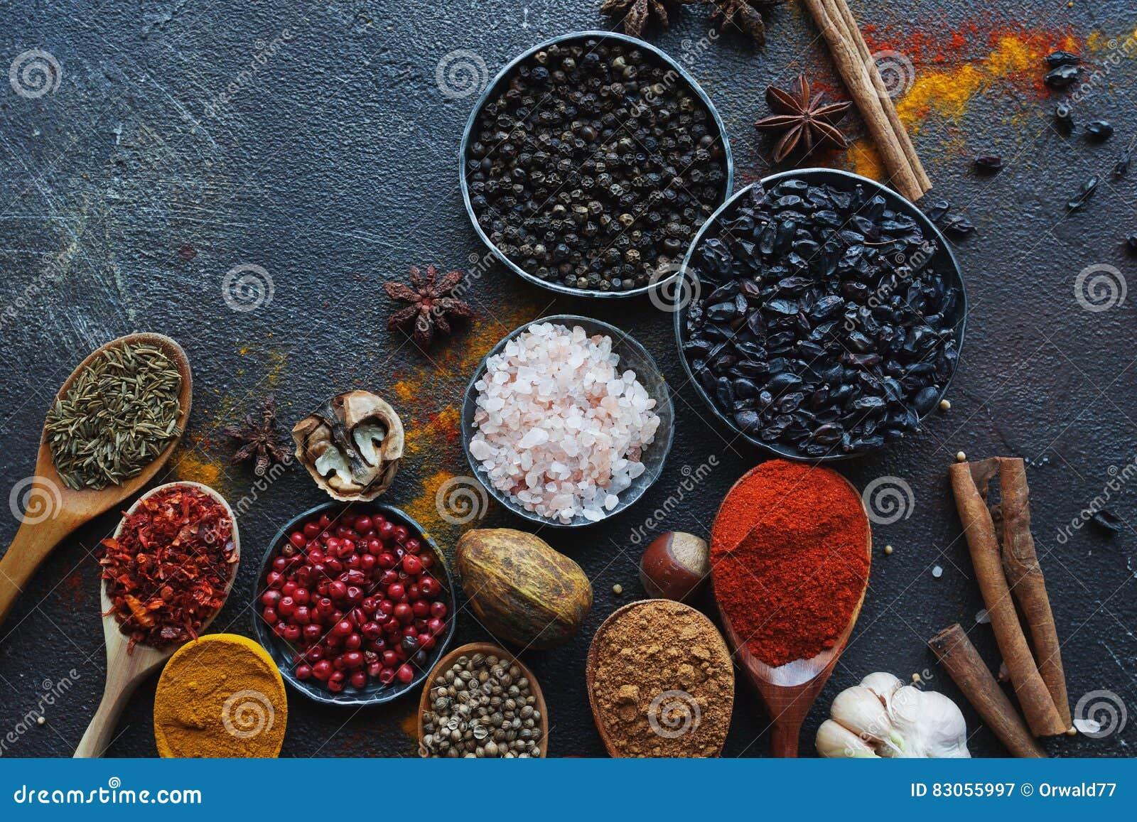 Várias especiarias indianas em colheres e bacias e porcas de madeira do metal na tabela de pedra escura Especiarias coloridas, vi