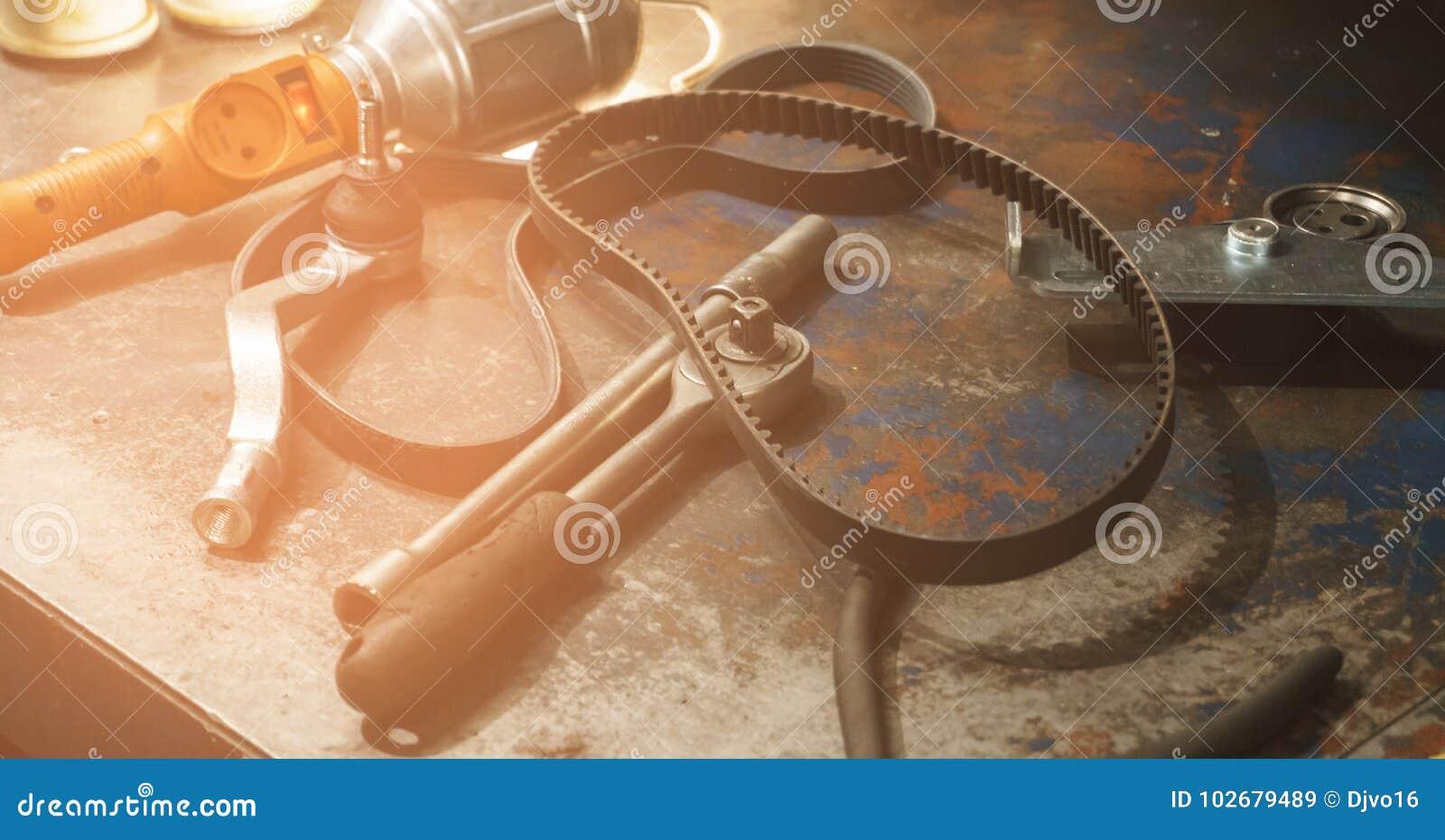 Várias ferramentas e peças sobresselentes em uma tabela oxidada suja em uma auto oficina