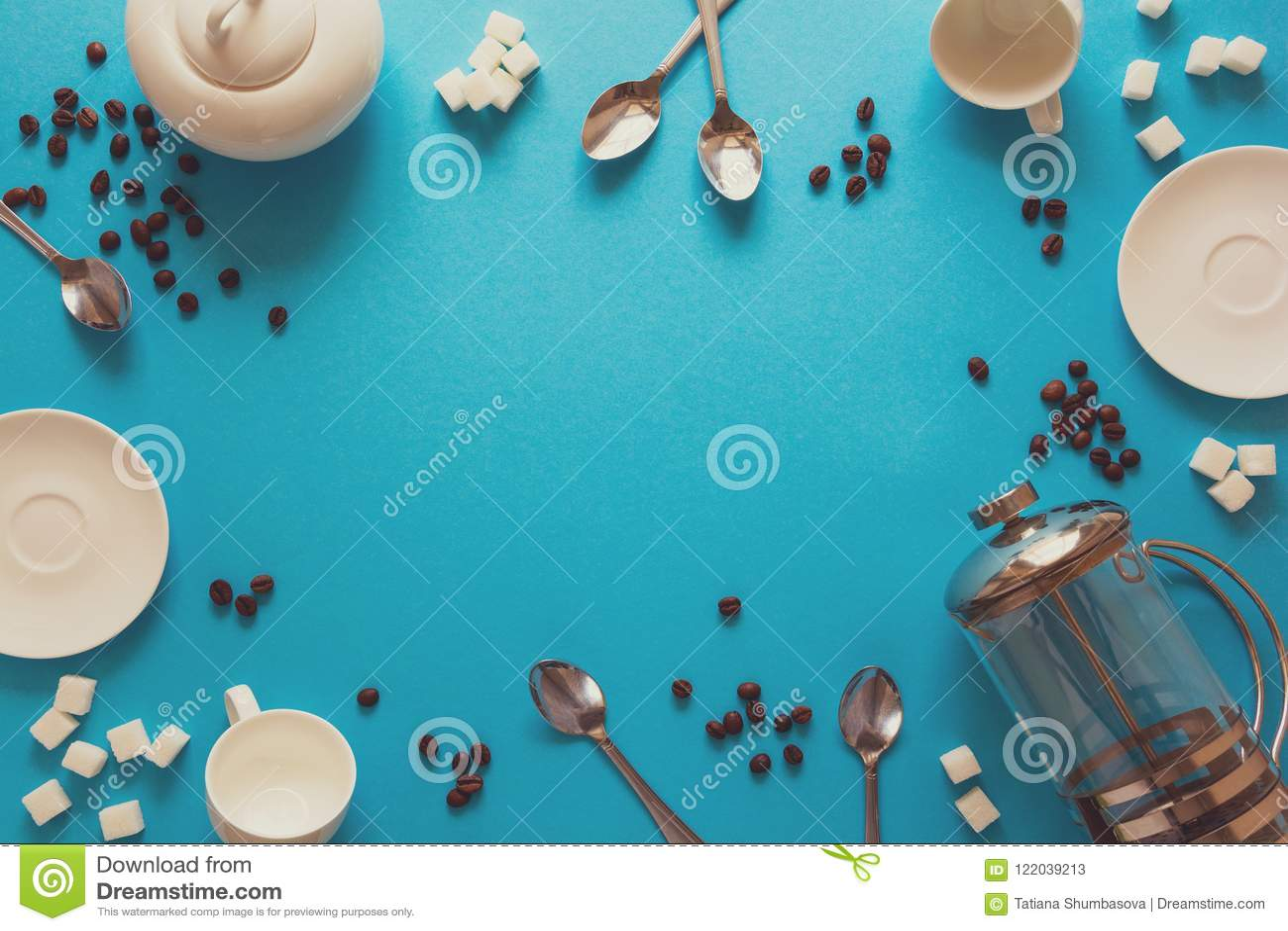 Vário café que faz acessórios: Imprensa do café, copos, pires, feijões de café, colheres e açúcar franceses no fundo do papel azu