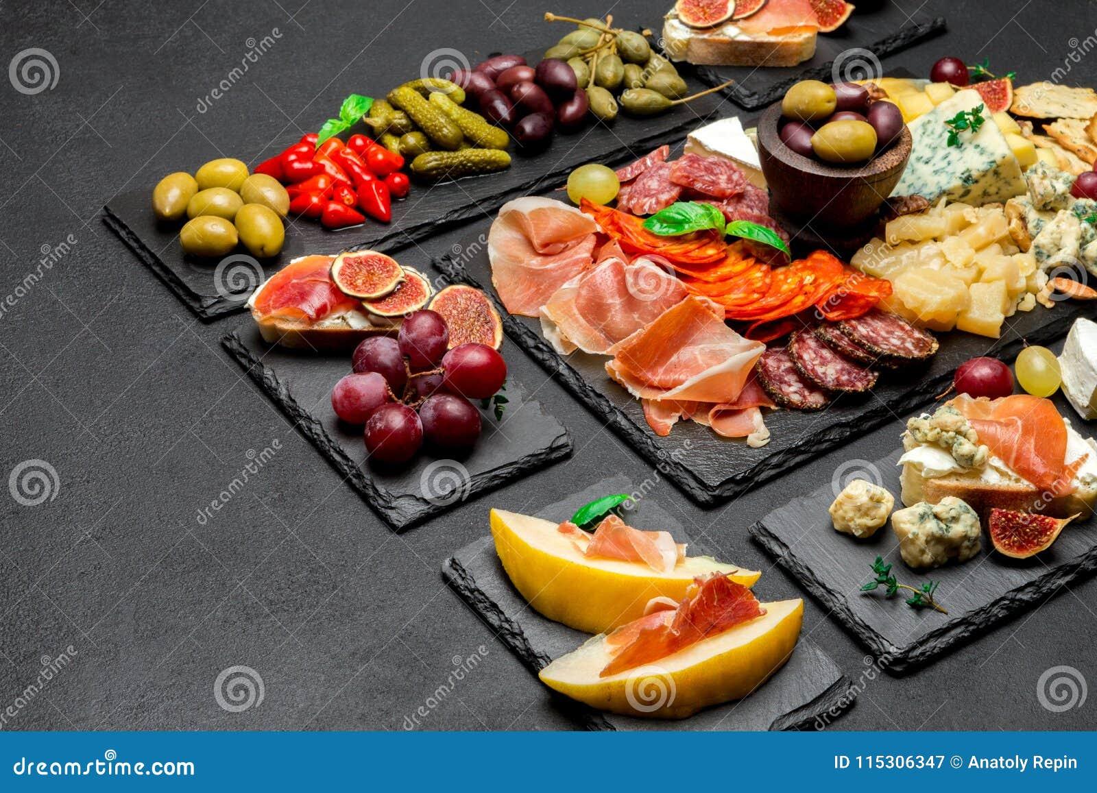 Vário tipo de refeição ou de petisco italiano - queijo, salsicha, azeitonas e parma