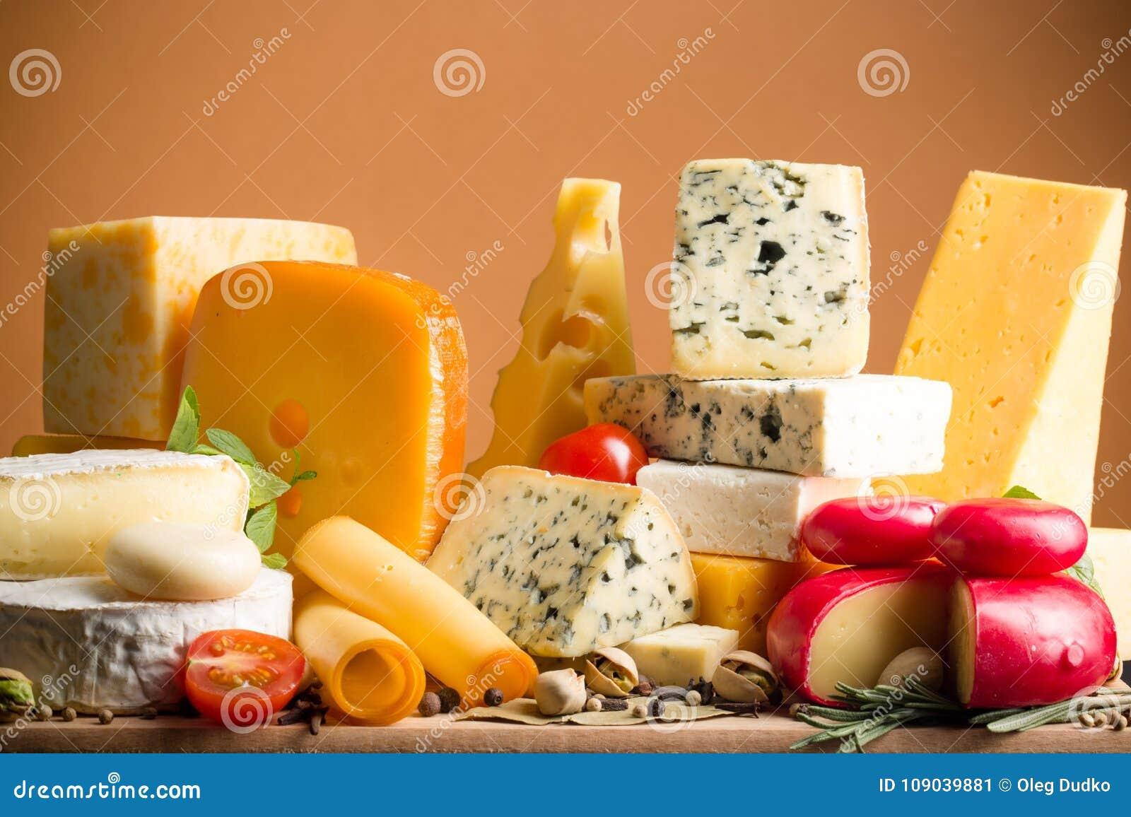 Vários tipos dos queijos na bandeja de madeira -