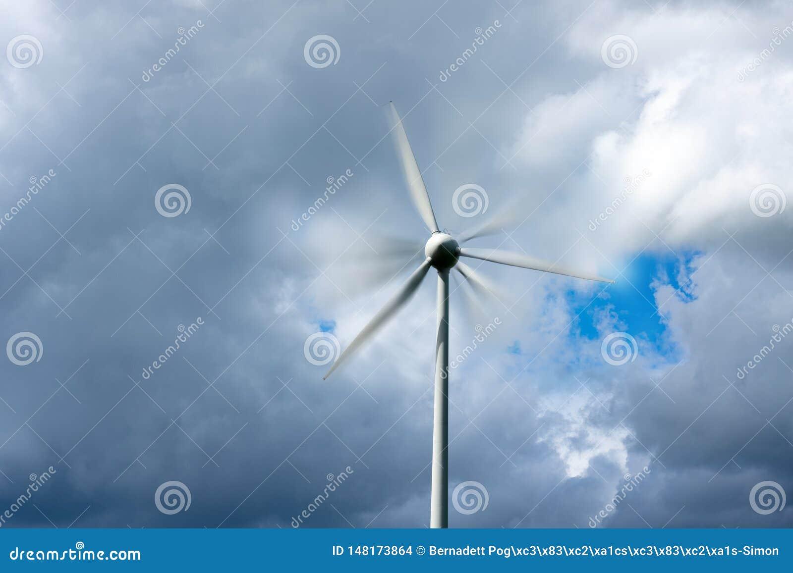 Väderkvarn för vindturbin med rörelsesuddighet och molnig himmel