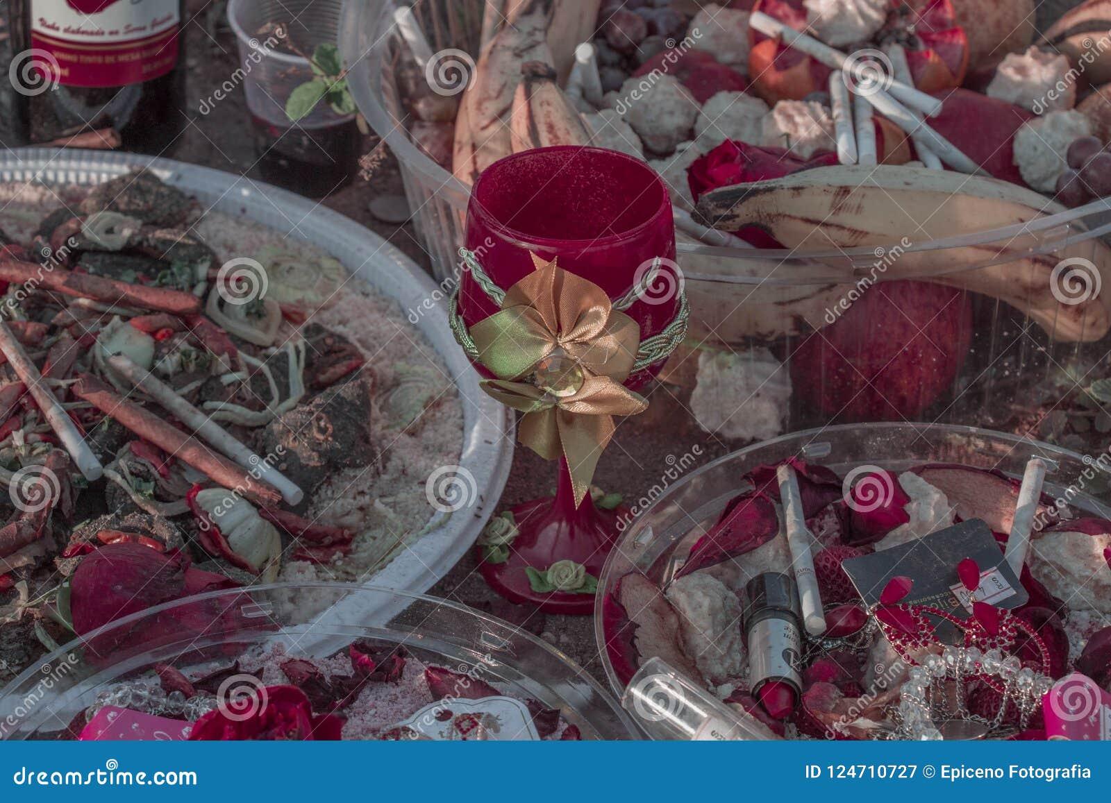 Vägrenvägren som erbjuder religion för Candomblé/UmbOffering Candomblé/Umbanda med rosor, cigarrettes och licquor