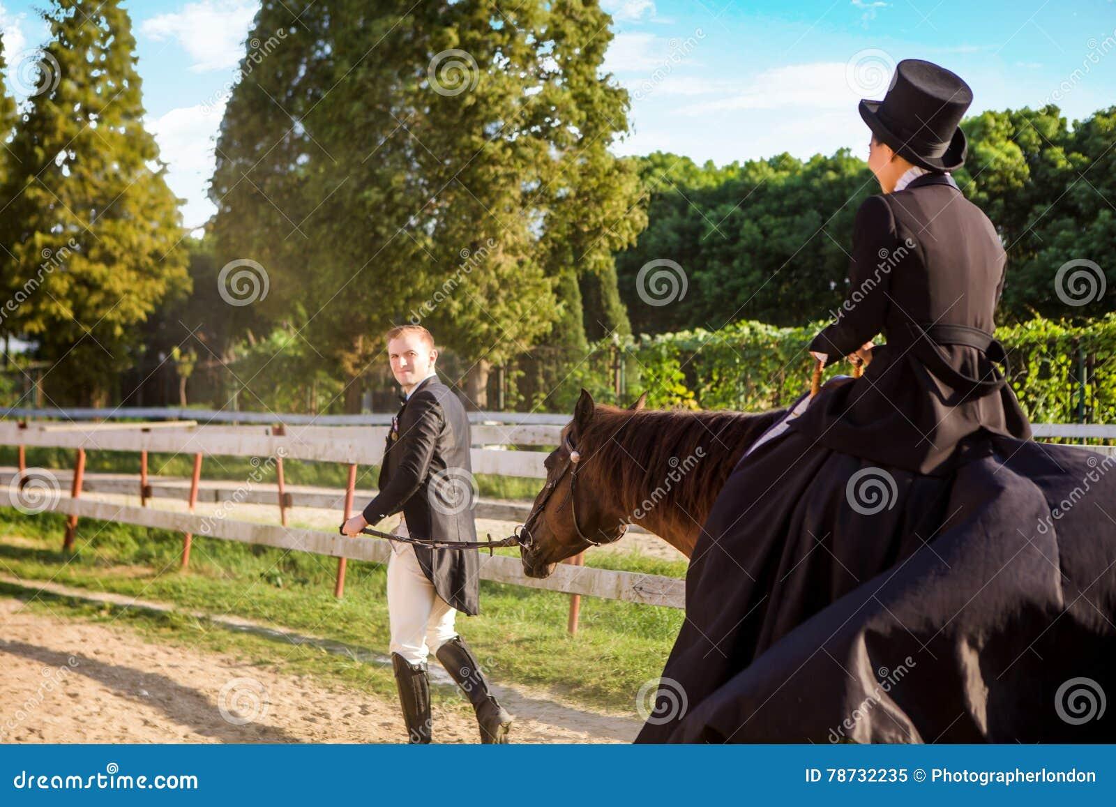 Välklädd man som drar kvinnasammanträde på häst på fältet