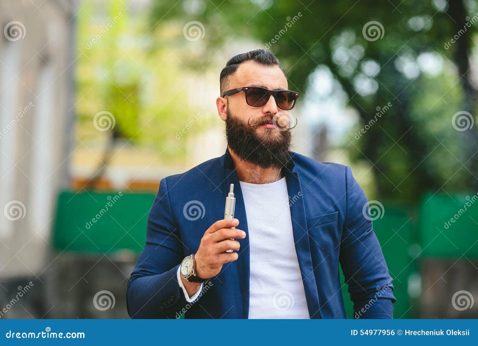 Välklädd man som röker den elektroniska cigaretten