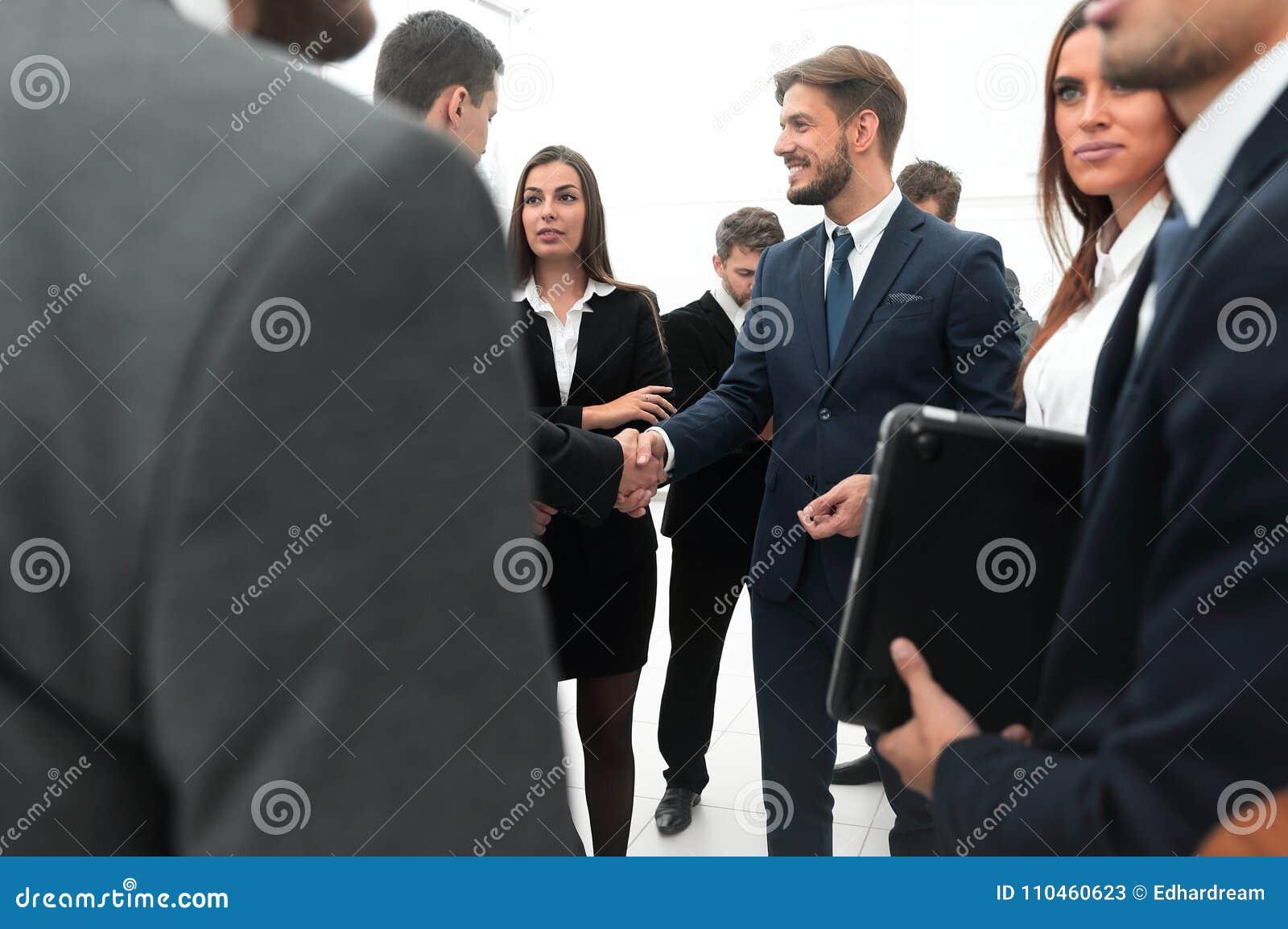 Välkomnande och handskakning av affärspartners i kontoret