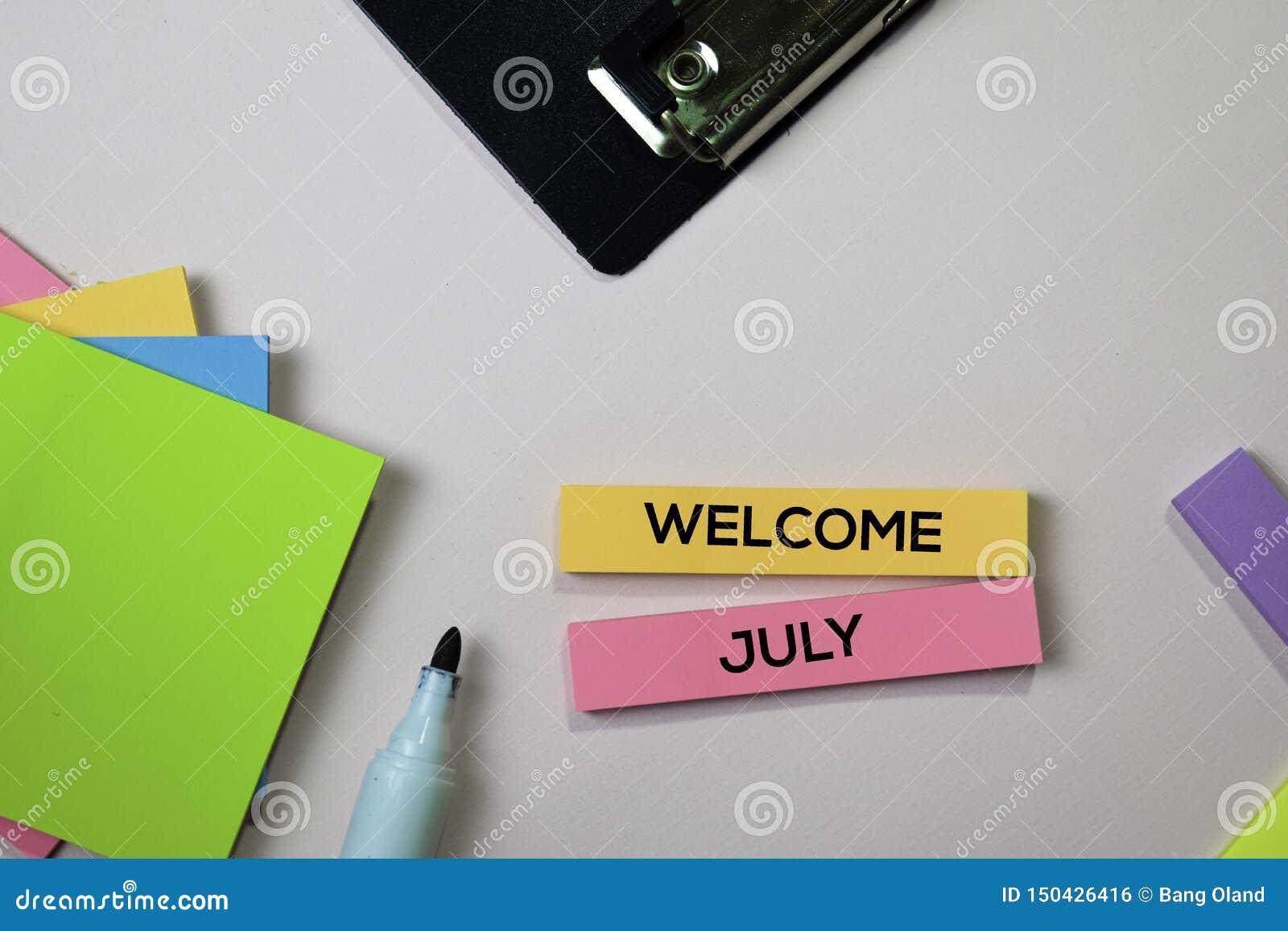 VälkomnandeJuli text på klibbiga anmärkningar med begrepp för kontorsskrivbord