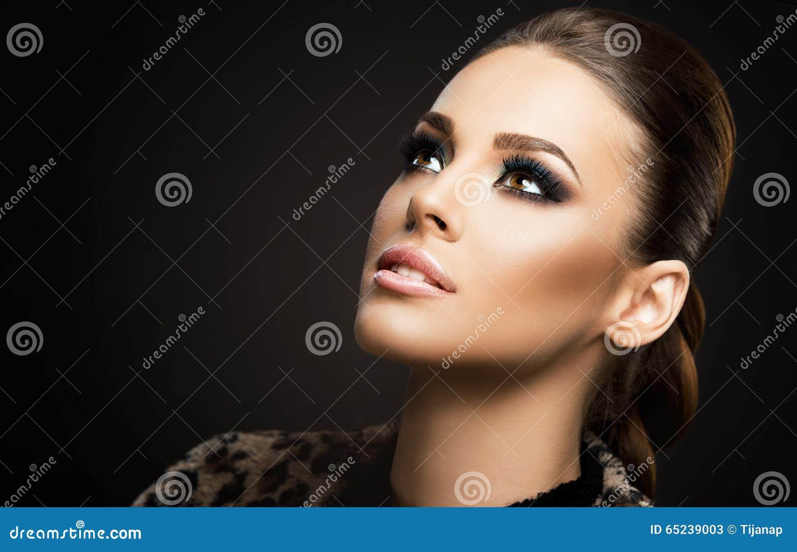 Vända mot närbilden av en härlig ung kvinna som isoleras på mörk bakgrund; göra perfekt hud, skönhetstående