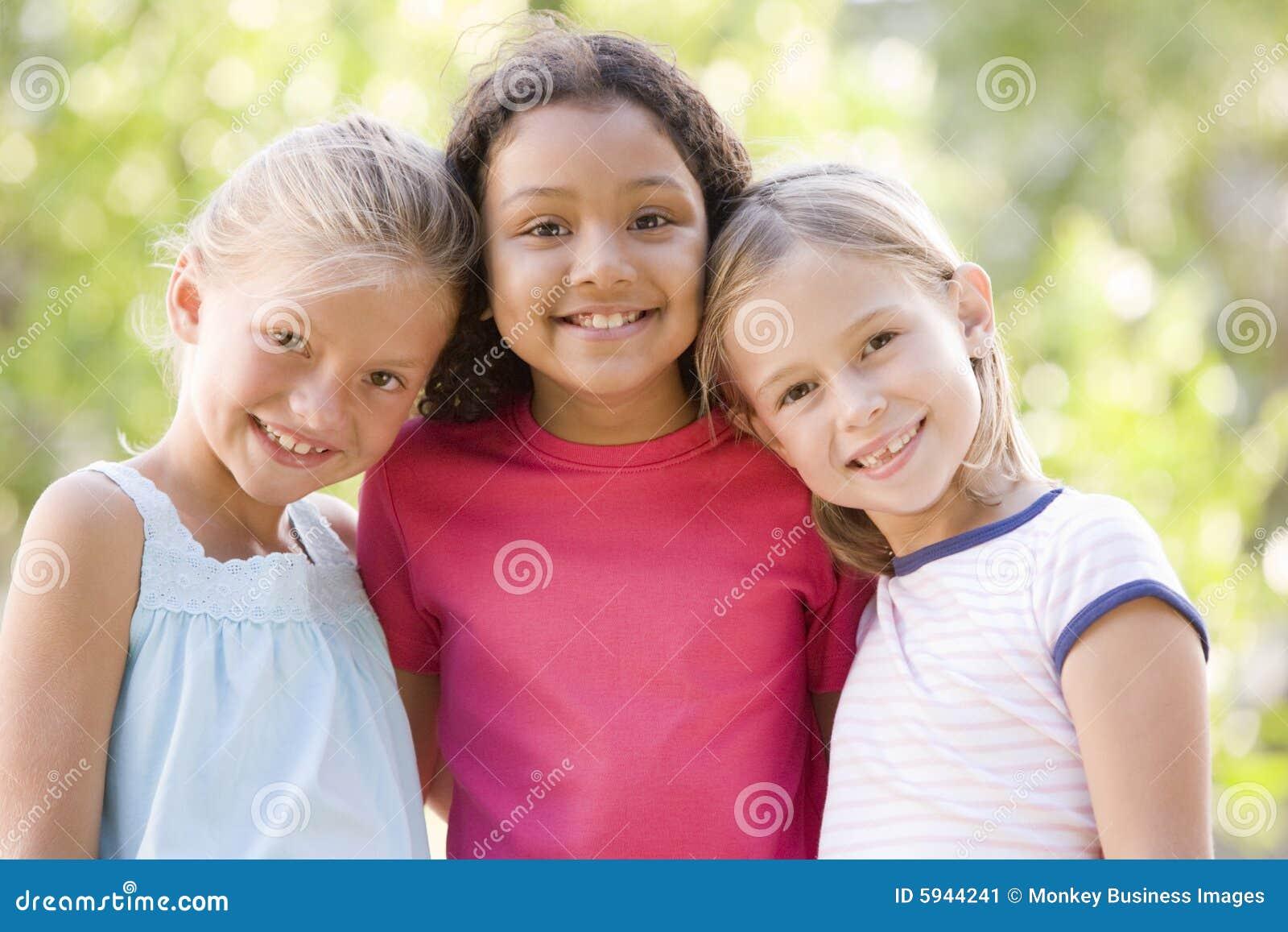Vänflicka som ler utomhus plattform tre barn