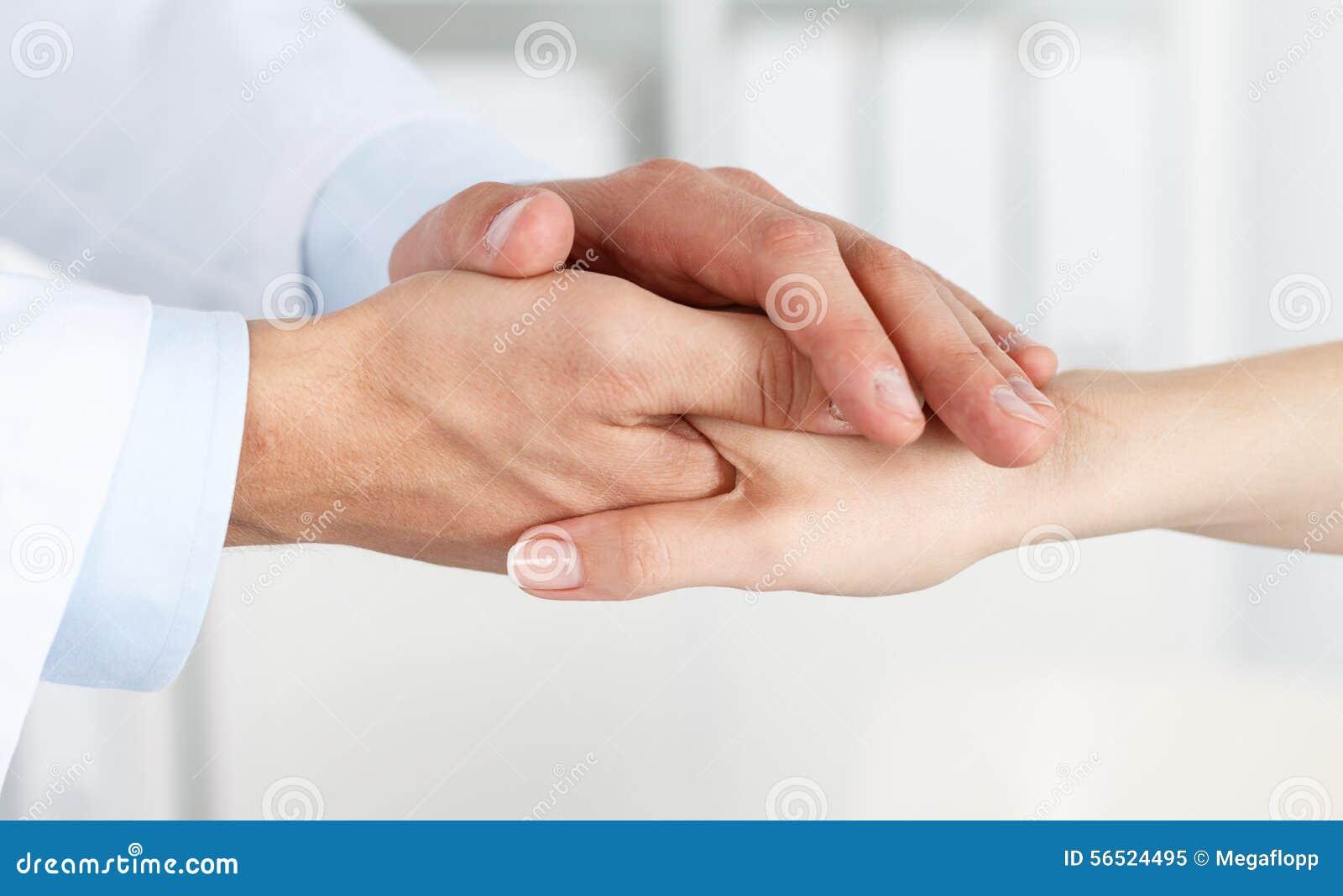 Vänliga manlig doktors händer som rymmer kvinnliga patients hand