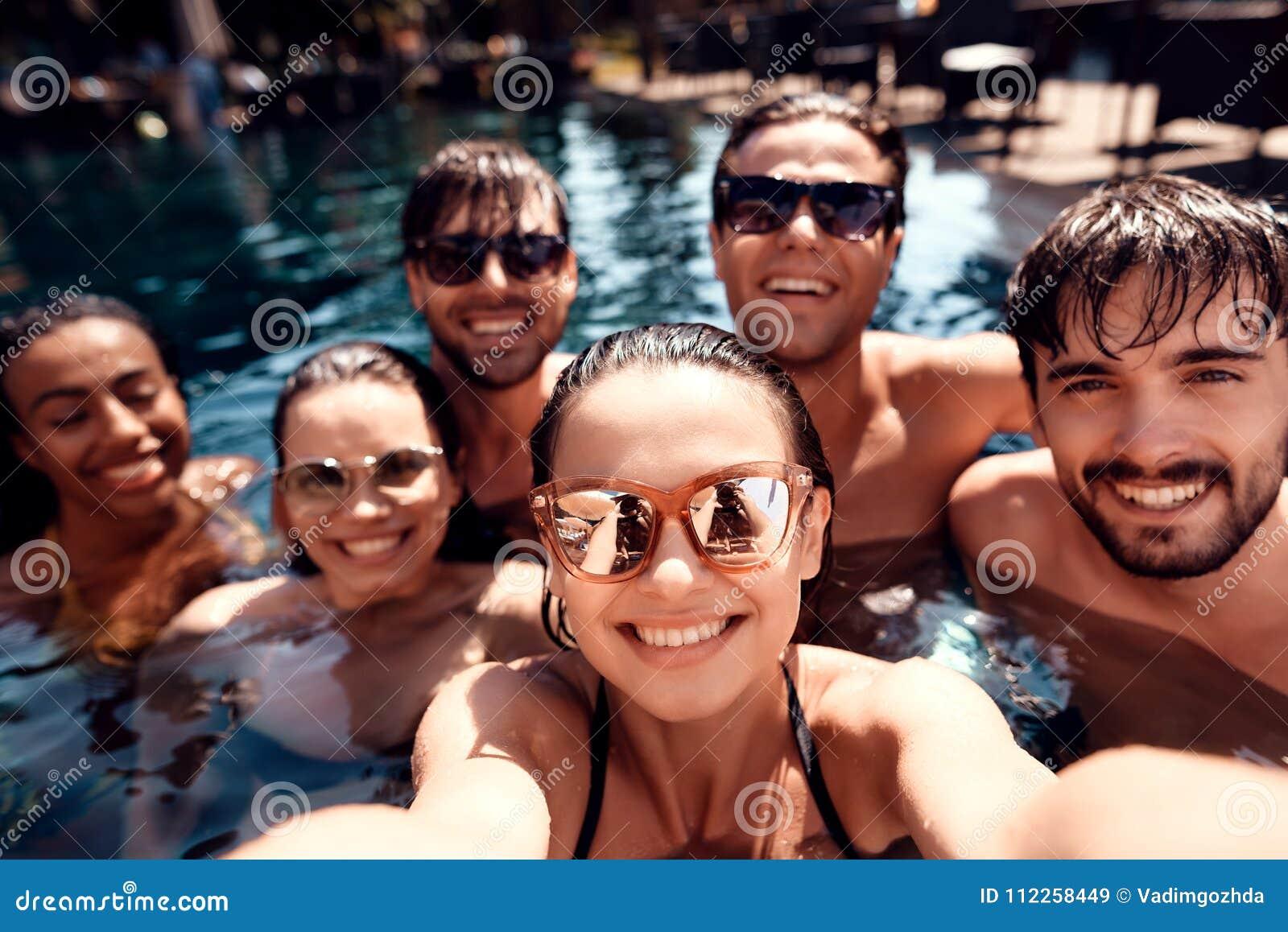 Vänner för sommarsemester tillsammans på simbassängpartiet Simbassängparti