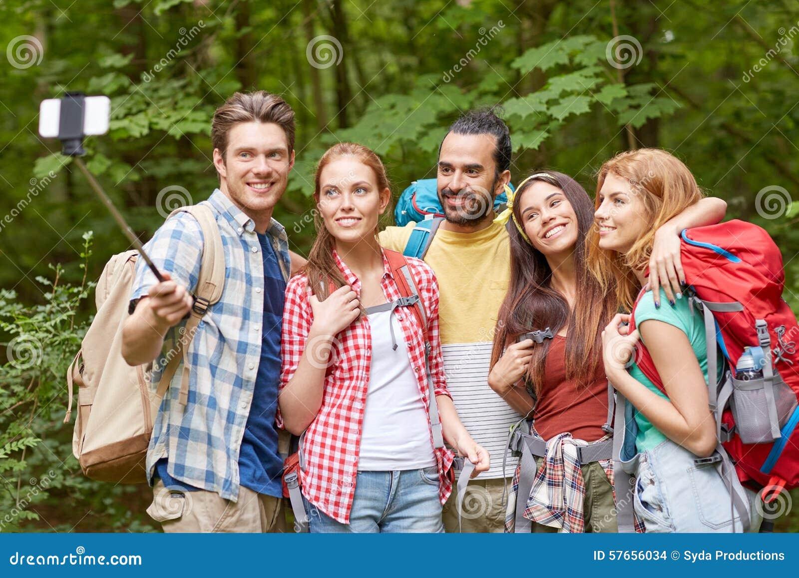 Vänner med ryggsäcken som tar selfie vid smartphonen