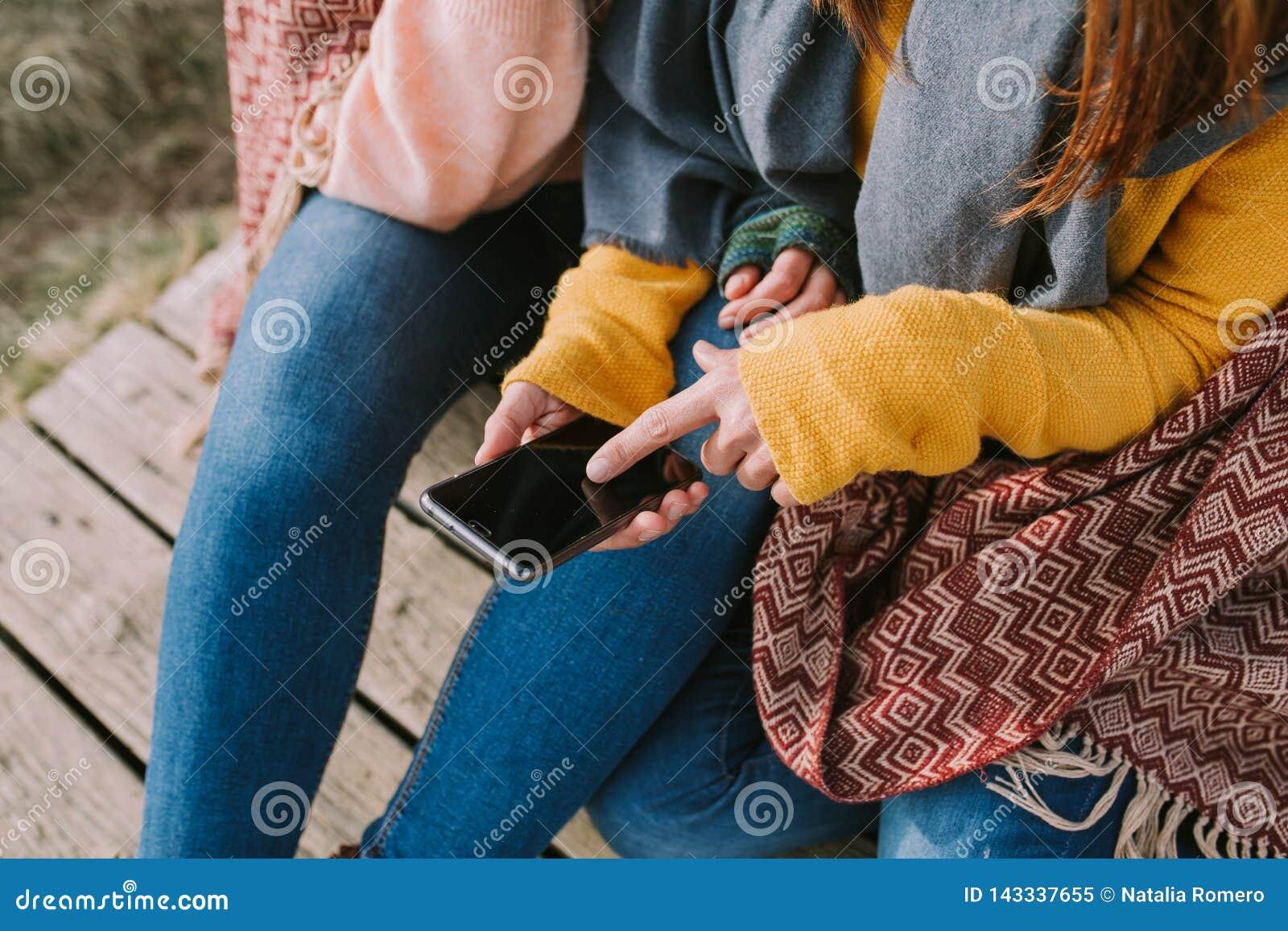 Vänner söker information på mobilen som de har i deras händer